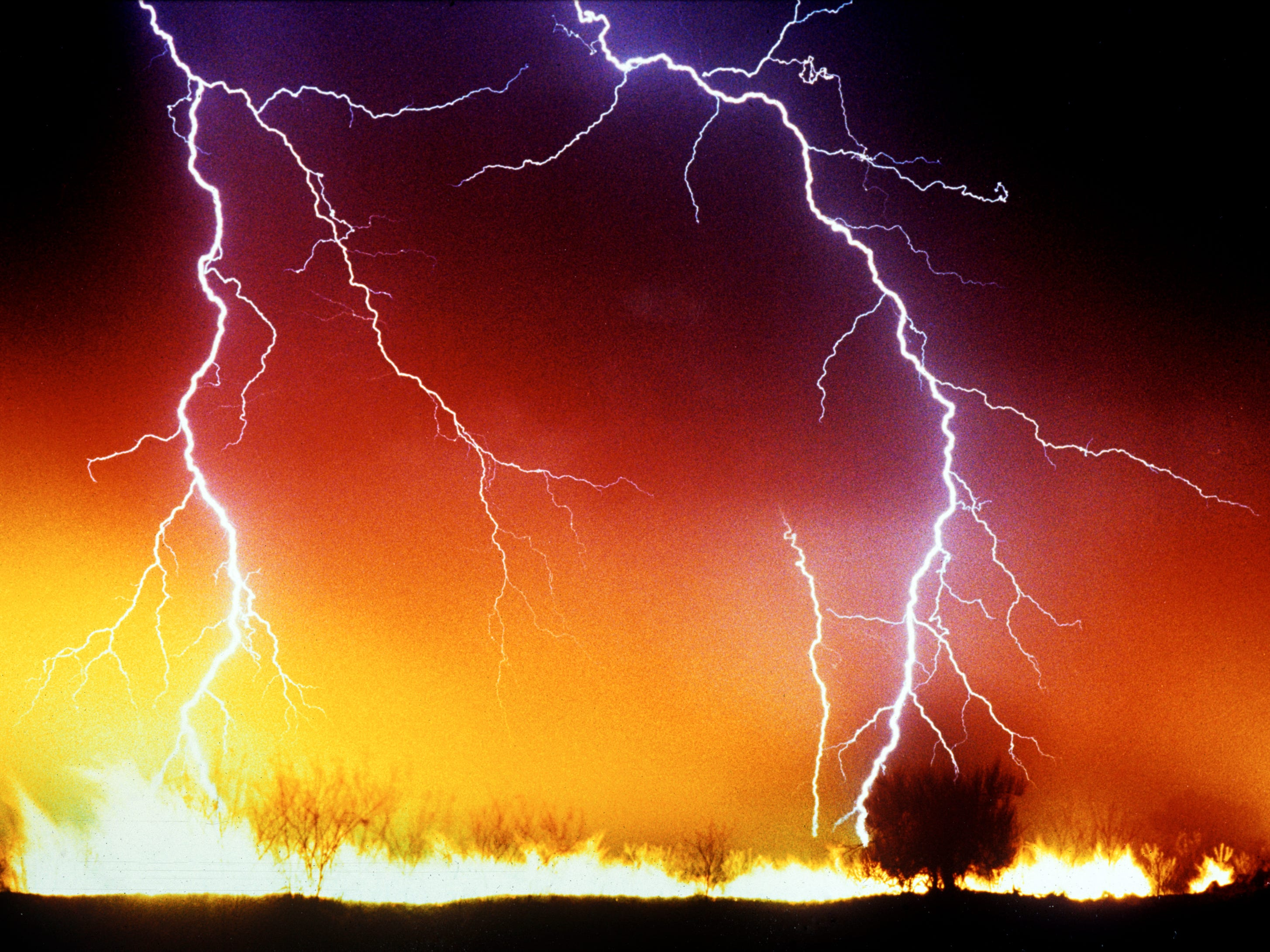 Lightning strikes over a brush fire on the Gila Indian Reservation.