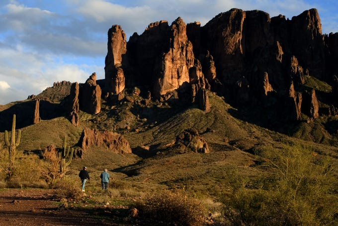 Hikers follow a trail leading to the Superstition Mountains at Lost Dutchman State Park north of Apache Junction.