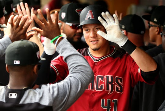 Arizona Diamondbacks Wilmer Flores (41) receives high-fives after hitting a two-run home run against the Cleveland Indians in the 1st inning during a spring training game on Mar. 7, 2019 at Salt River Fields in Scottsdale, Ariz.