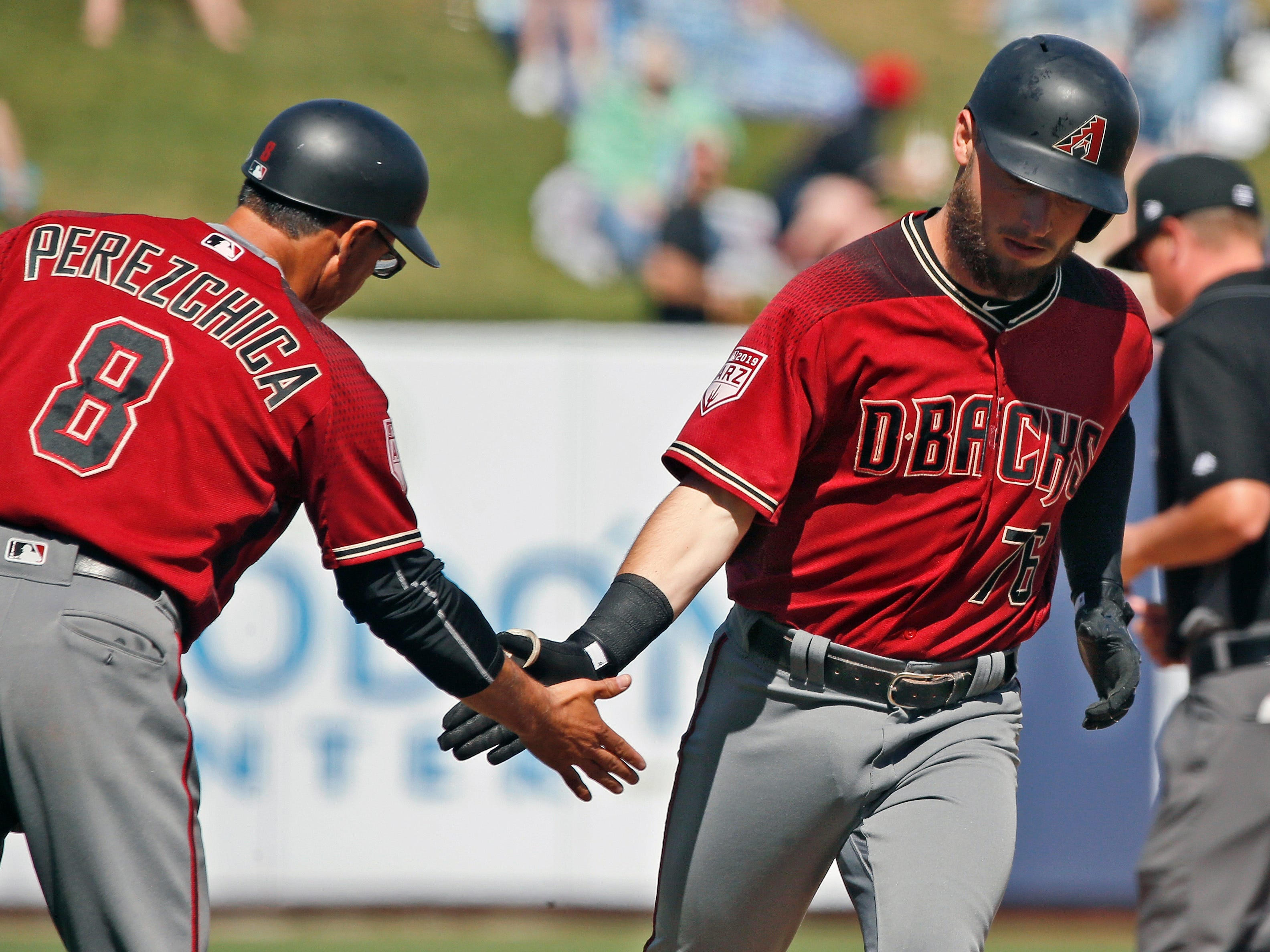 Arizona Diamondbacks' Wyatt Mathisen (76) is congratulated by third base coach Tony Perezchica (8) after hitting a solo home run in the seventh inning of a spring training baseball game against the Milwaukee Brewers, Friday, March 8, 2019, in Phoenix.
