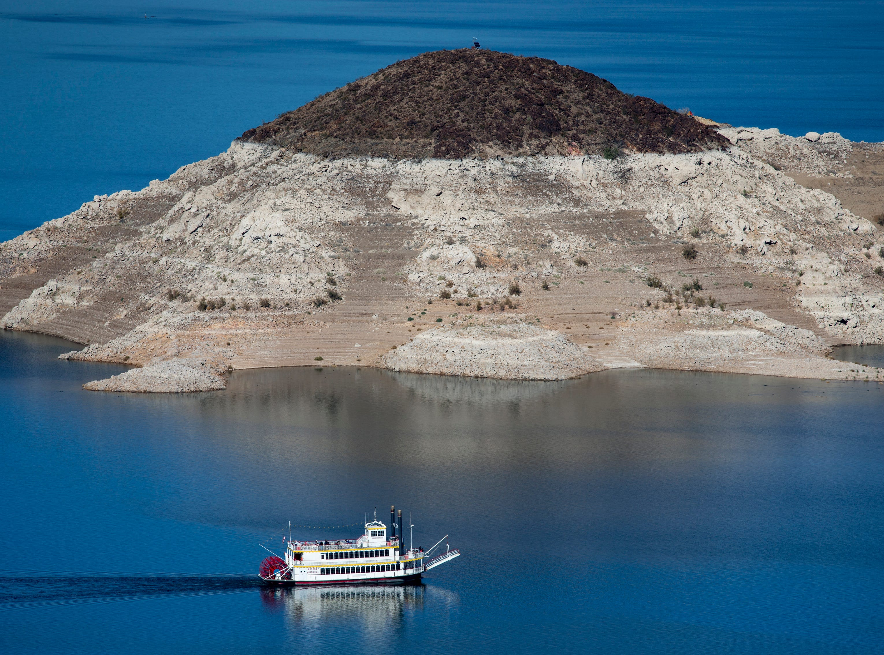 """The Desert Princess, a three-level paddle-wheeler, passes Rock Island, November 17, 2014, while leaving Hemenway Harbor on a mid-day sightseeing cruse.  A high-water mark or """"bathtub ring"""" is visible on the shoreline; Lake Mead is down over 145 vertical feet."""