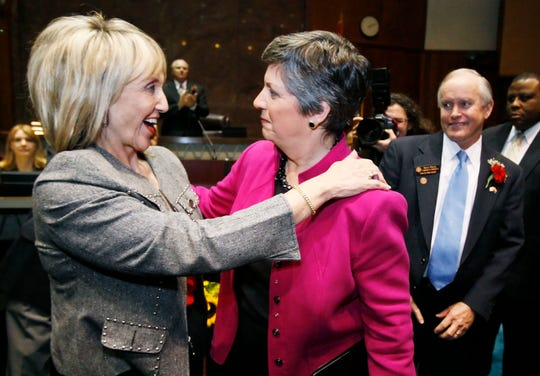 Republican Jan Brewer (left) hugs outgoing Democratic Gov. Janet Napolitano in 2009 after Napolitano gave her final State of the State address.