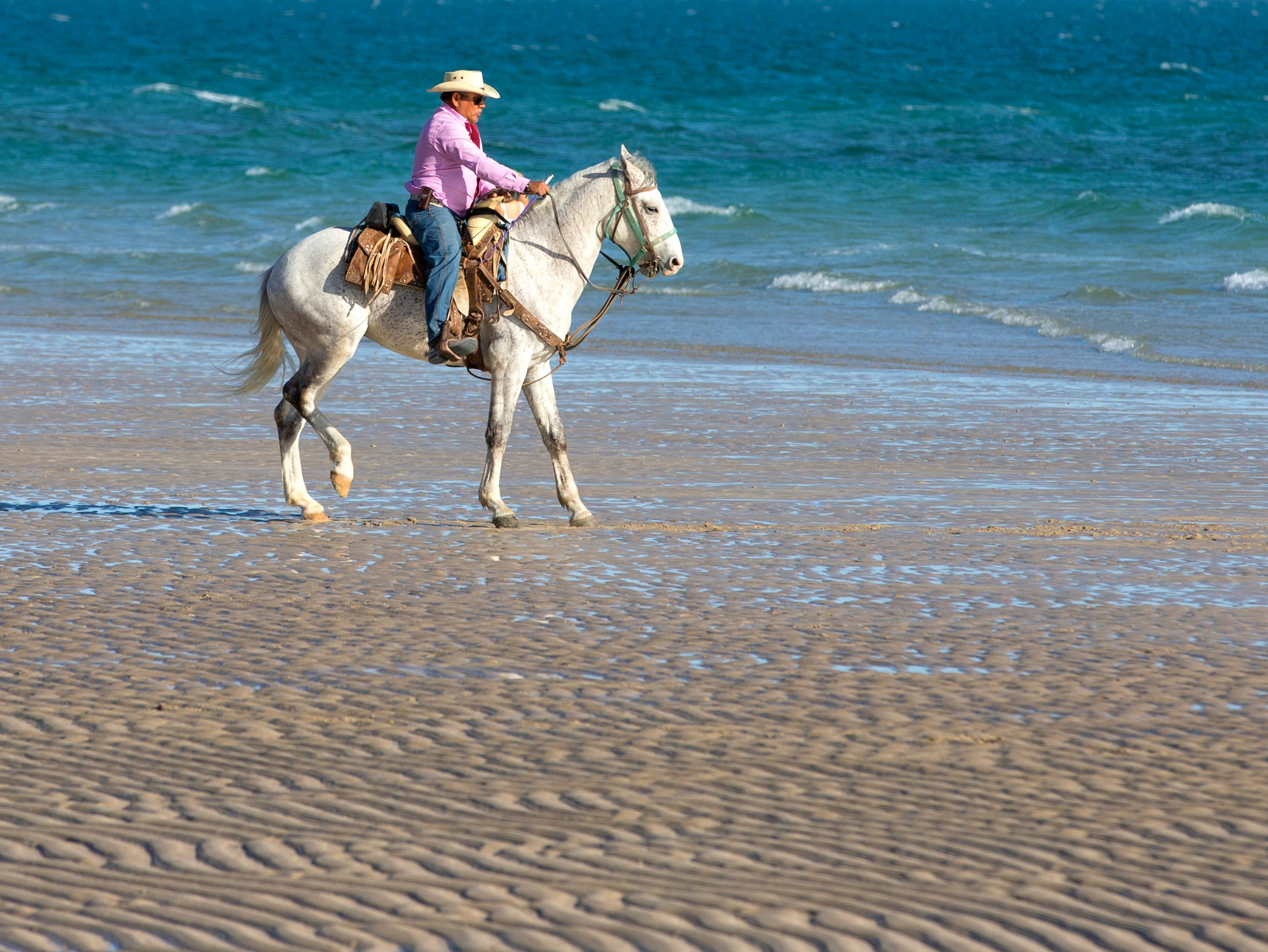 Clemente Vasquez Montoya rides his horse, Morro,  on Sandy Beach in Puerto Penasco, Mexico. Montoya rents horses for riding on the beach.