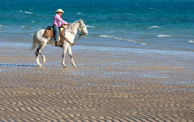 Clemente Vasquez Montoya rides his horse, Morro,  on Sandy Beach in Puerto Penasco, Mexico. Montoya rents horses for riding on the beach.