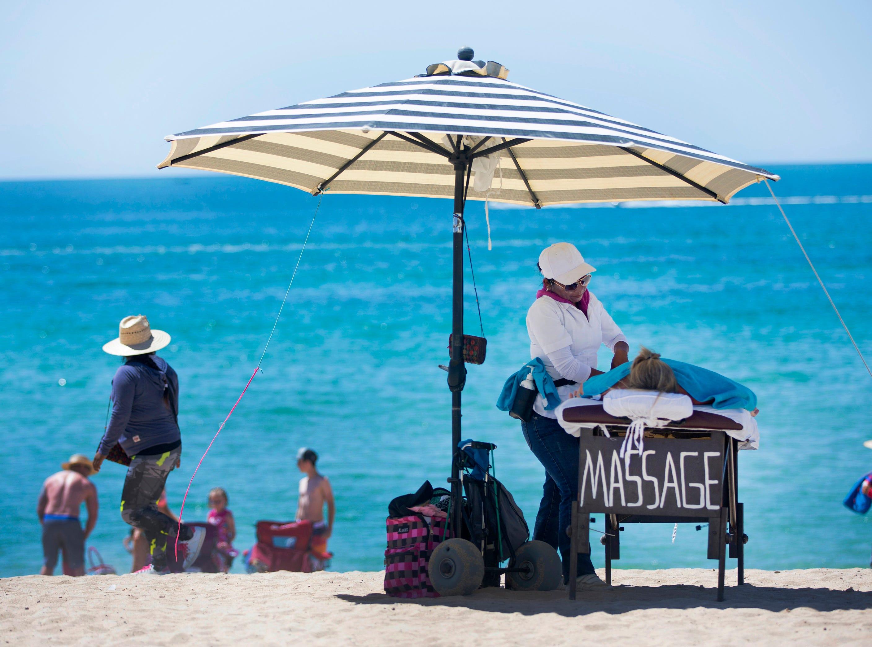 Jan Kortsen, of Thatcher, Az., gets a massage from Connie Clemente on Sandy Beach in Puerto Penasco, Mexico.