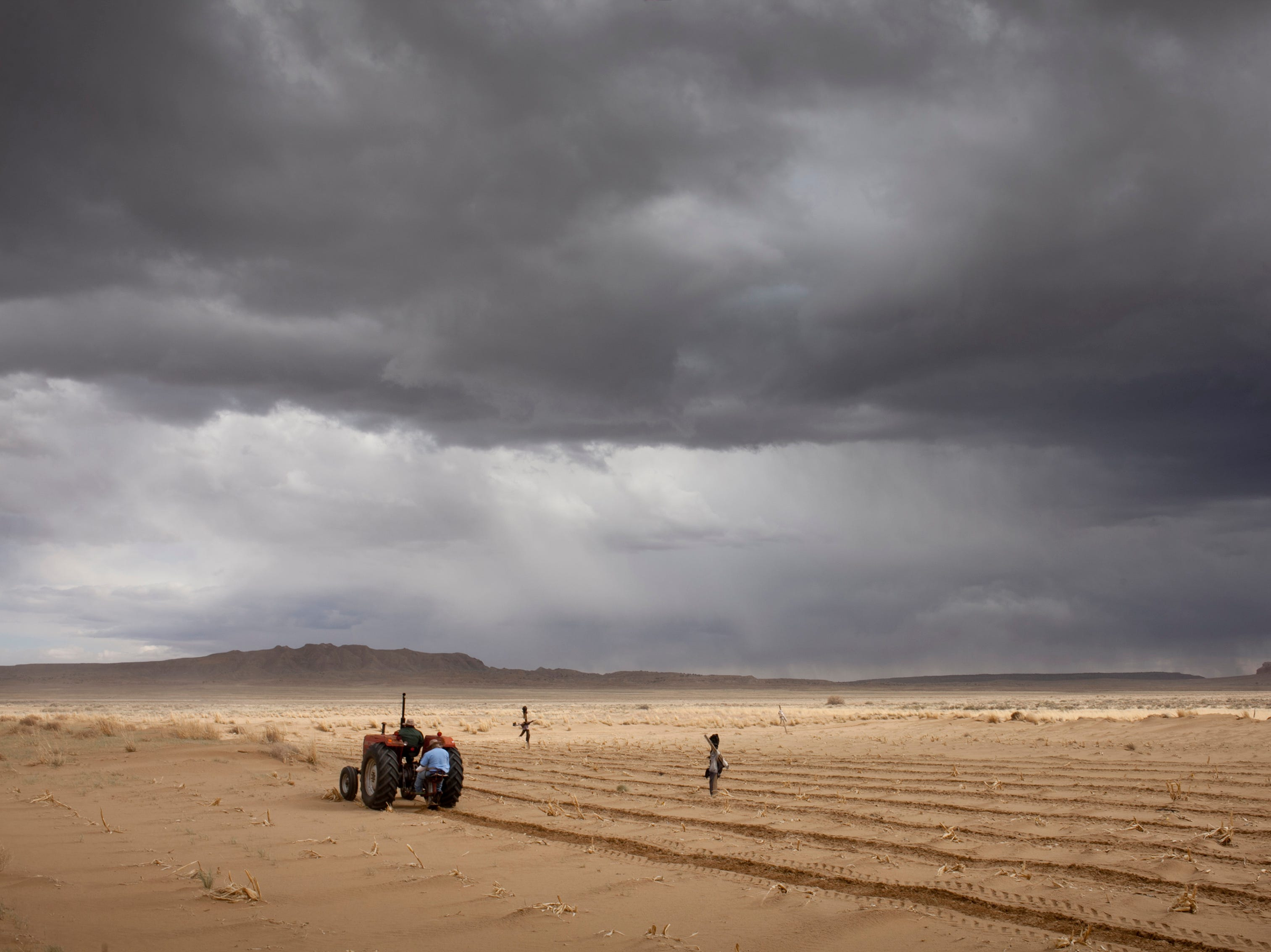 An storm approaches as Watson Honanie and Lester Honavema plant blue corn in their sandy desert fields located eight miles southwest of Hotevilla.