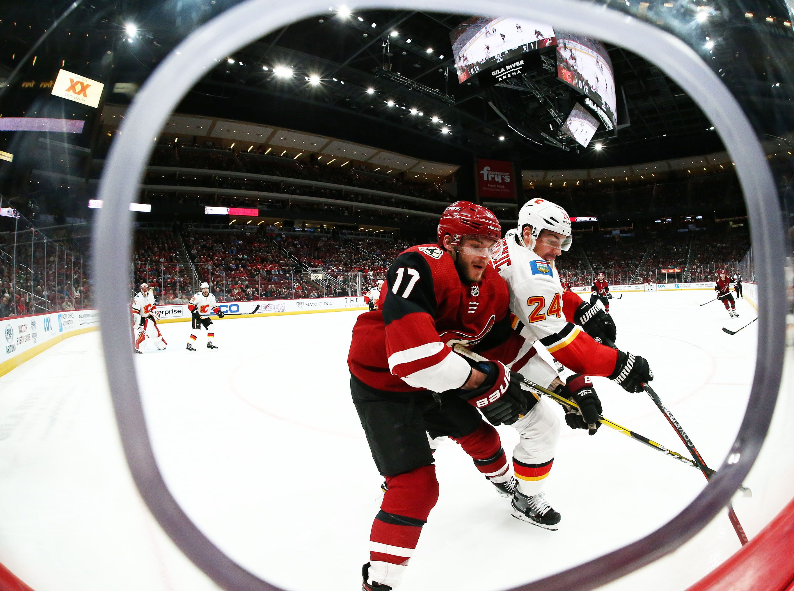 Arizona Coyotes center Alex Galchenyuk (17) and Calgary Flames defenseman Travis Hamonic (24) chase the puck in the second period on Mar. 7, 2019, at Gila River Arena in Glendale, Ariz.