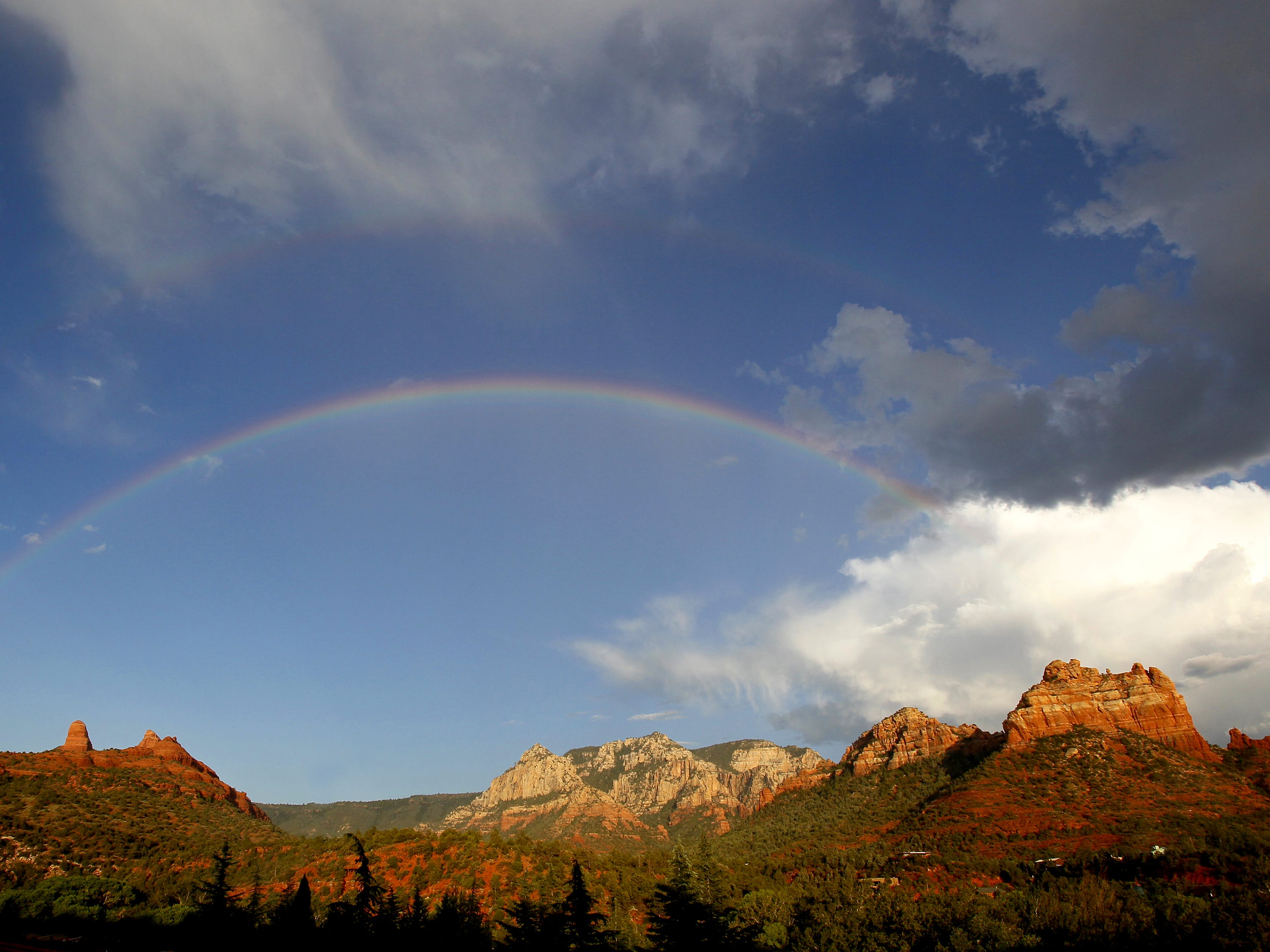 A rainbow arching over the red rocks in Sedona after summer storm.