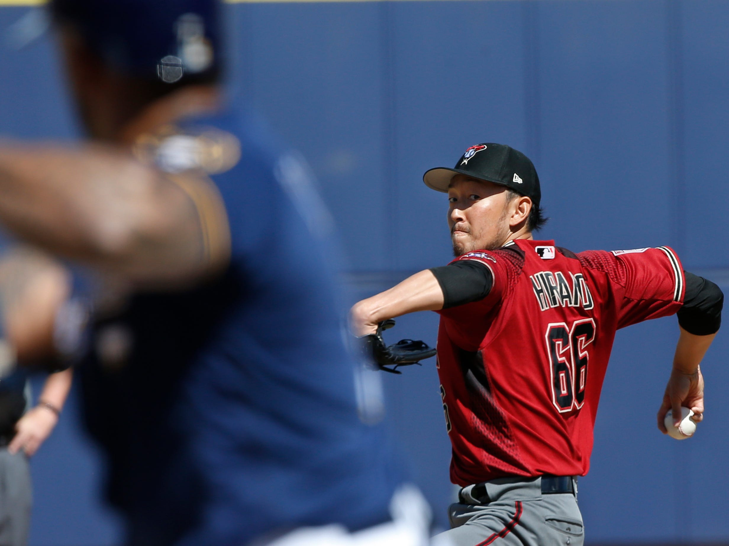 Arizona Diamondbacks relief pitcher Yoshihisa Hirano (66) delivers to Milwaukee Brewers' Eric Thames, left, in the sixth inning of a spring training baseball game Friday, March 8, 2019, in Phoenix.