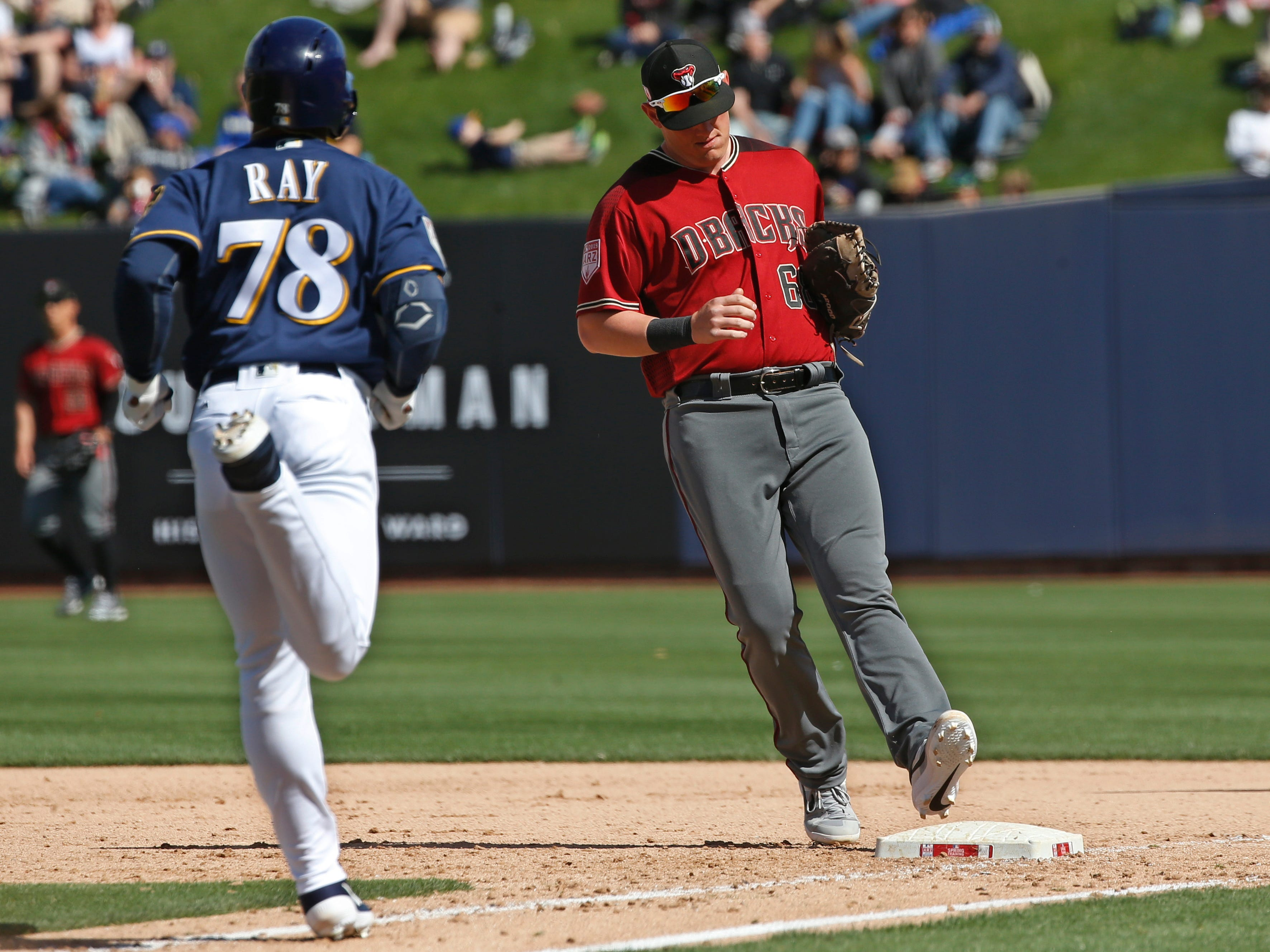 Arizona Diamondbacks first baseman Kevin Cron (68) forces out Milwaukee Brewers' Corey Ray (78) unassisted on a ground ball in the seventh inning of a spring training baseball game Friday, March 8, 2019, in Phoenix.