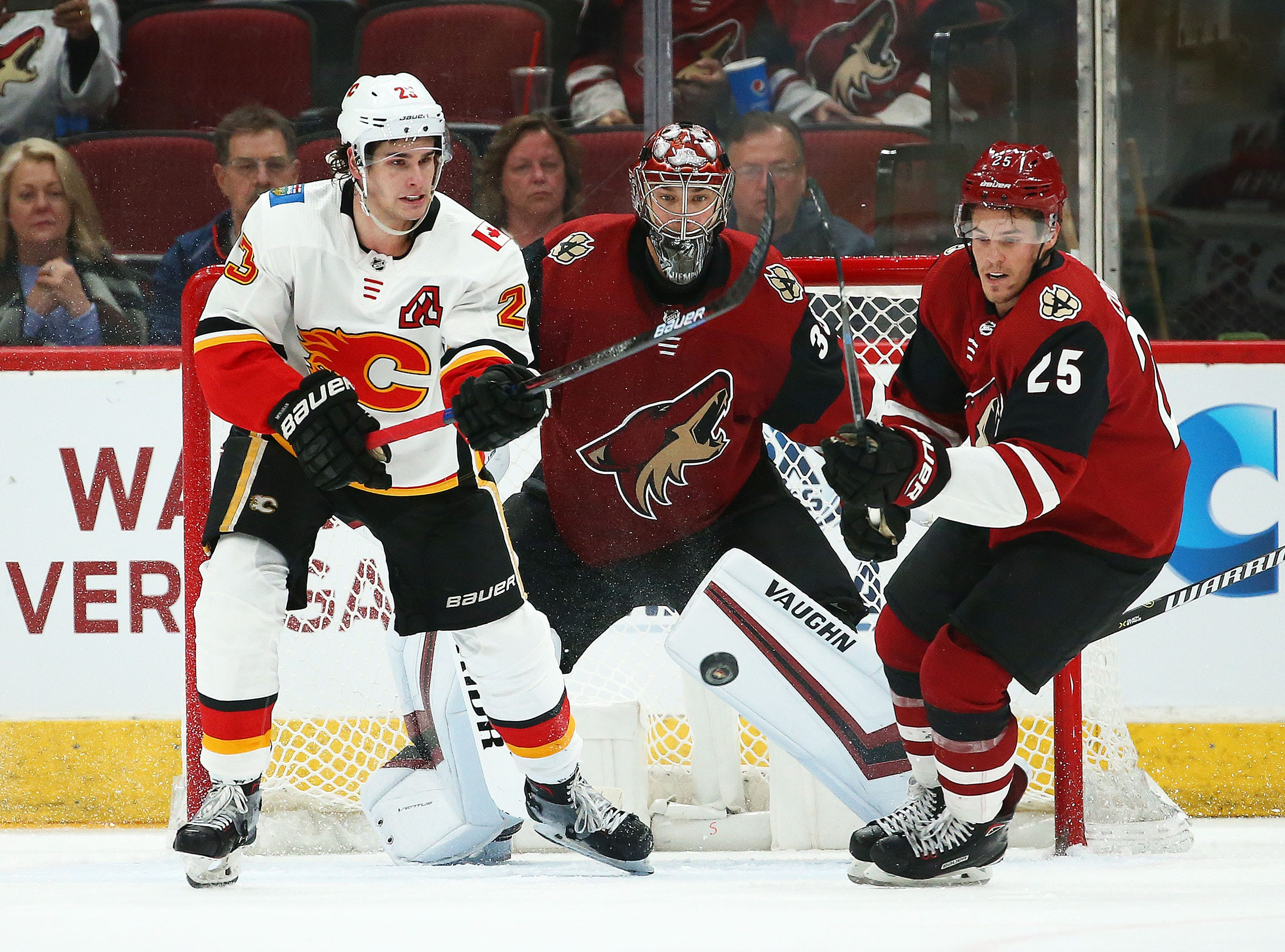 Calgary Flames center Sean Monahan (23) and Arizona Coyotes goaltender Darcy Kuemper (35) and center Nick Cousins (25) watch the puck in the second period on Mar. 7, 2019, at Gila River Arena in Glendale, Ariz.