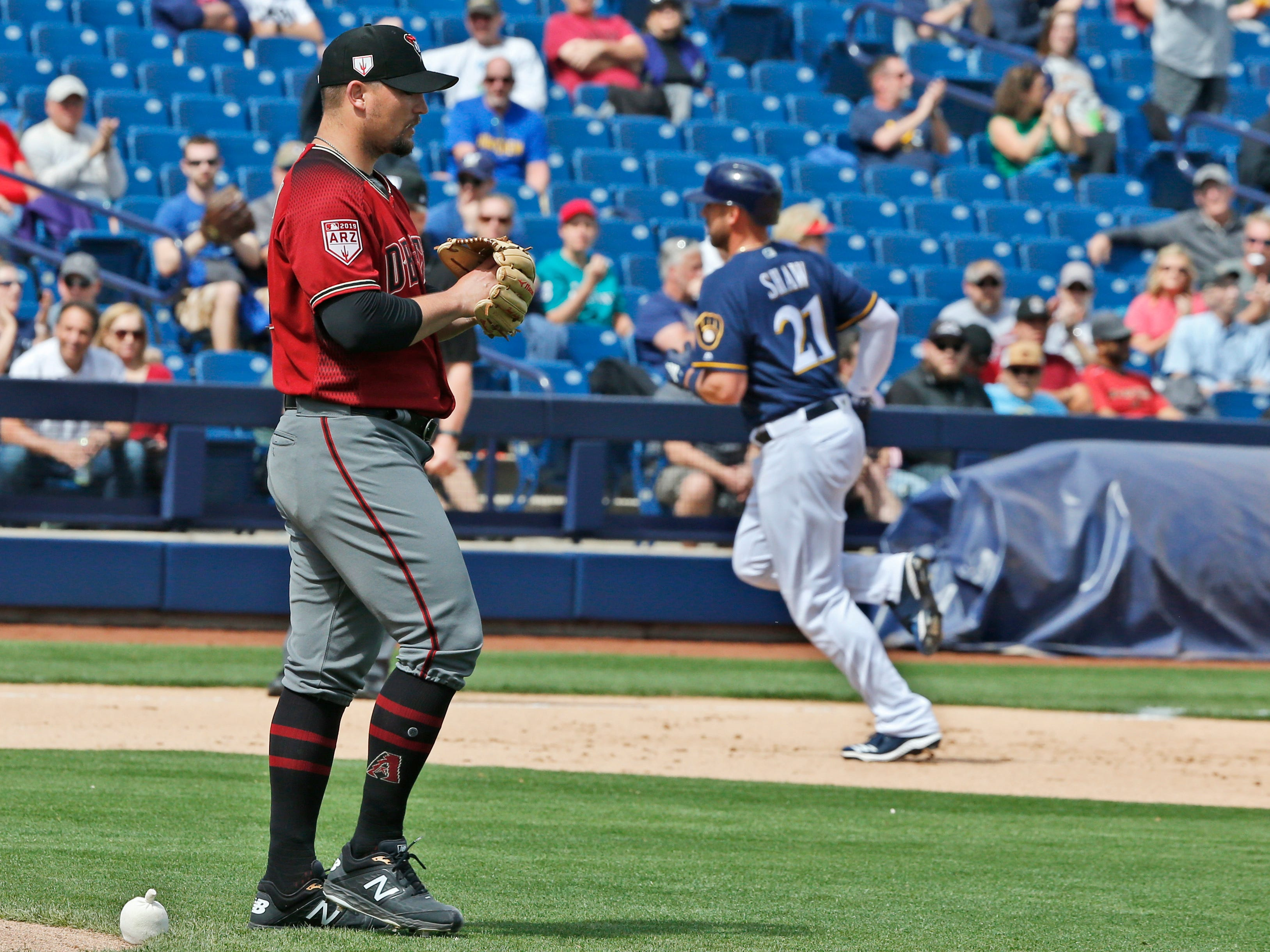 Arizona Diamondbacks starting pitcher Zack Godley, left, walks off the back of the mound as Milwaukee Brewers' Travis Shaw (21) runs the bases following a home run in the fourth inning of a spring training baseball game Friday, March 8, 2019, in Phoenix.