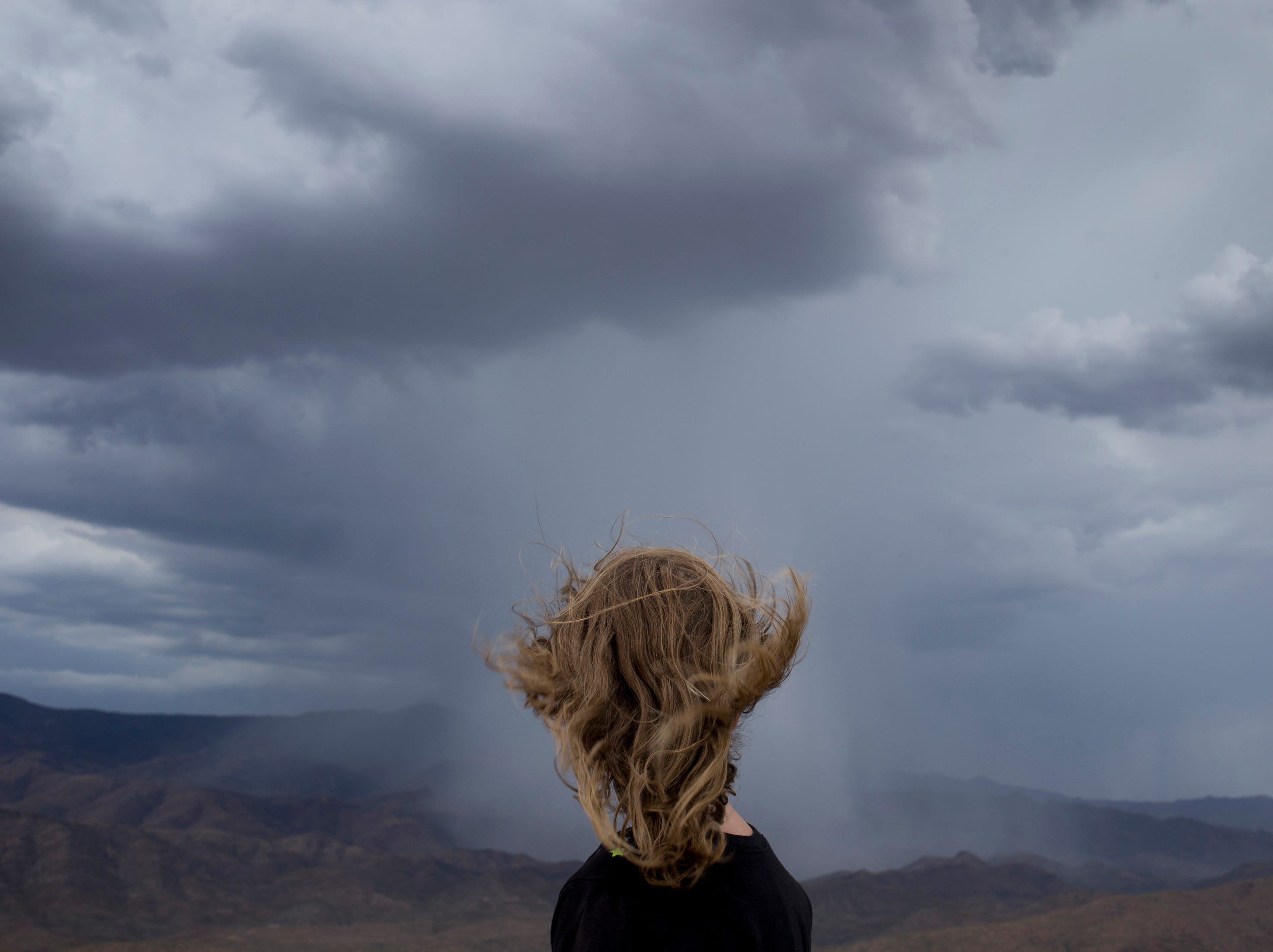 Loralie Rogers watches an approaching storm from Sunset Point Rest Area on I-17 north of Phoenix, Arizona.