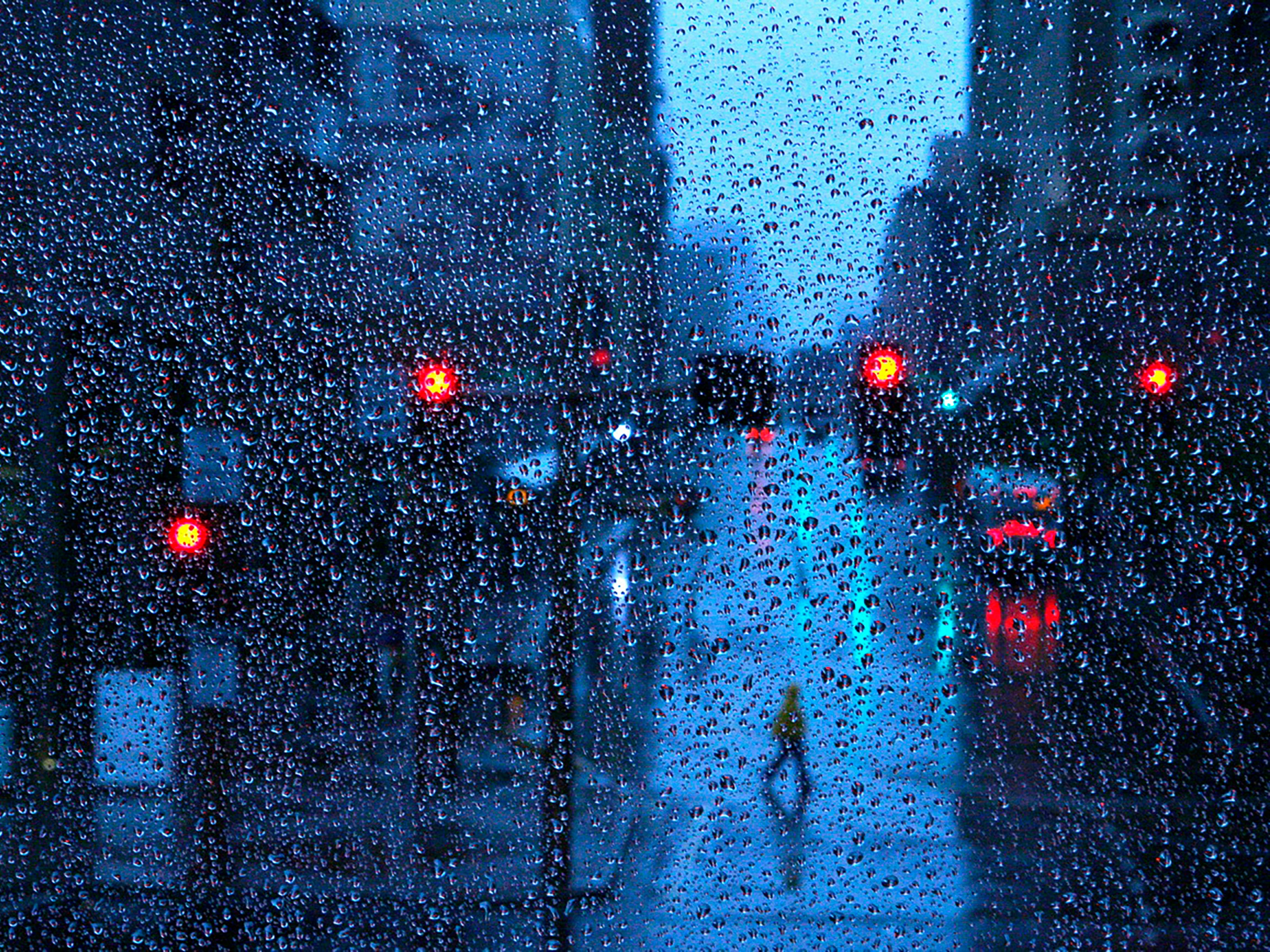 A pedestrian dodges rain drops as they cross Central in downtown Phoenix.