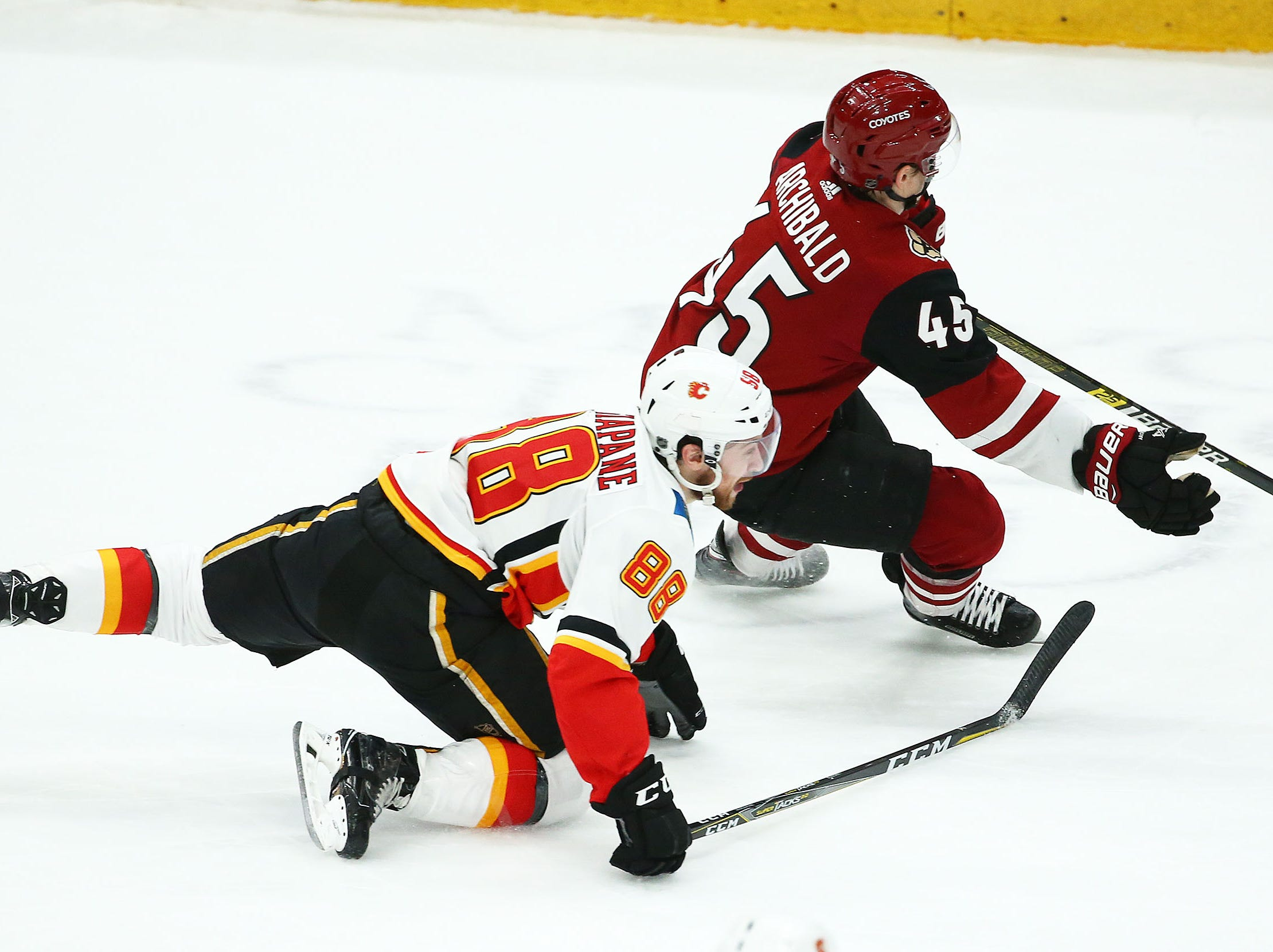 Calgary Flames left wing Andrew Mangiapane (88) battles for the puck with Arizona Coyotes right wing Josh Archibald (45) in the first period on Mar. 7, 2019, at Gila River Arena in Glendale, Ariz.