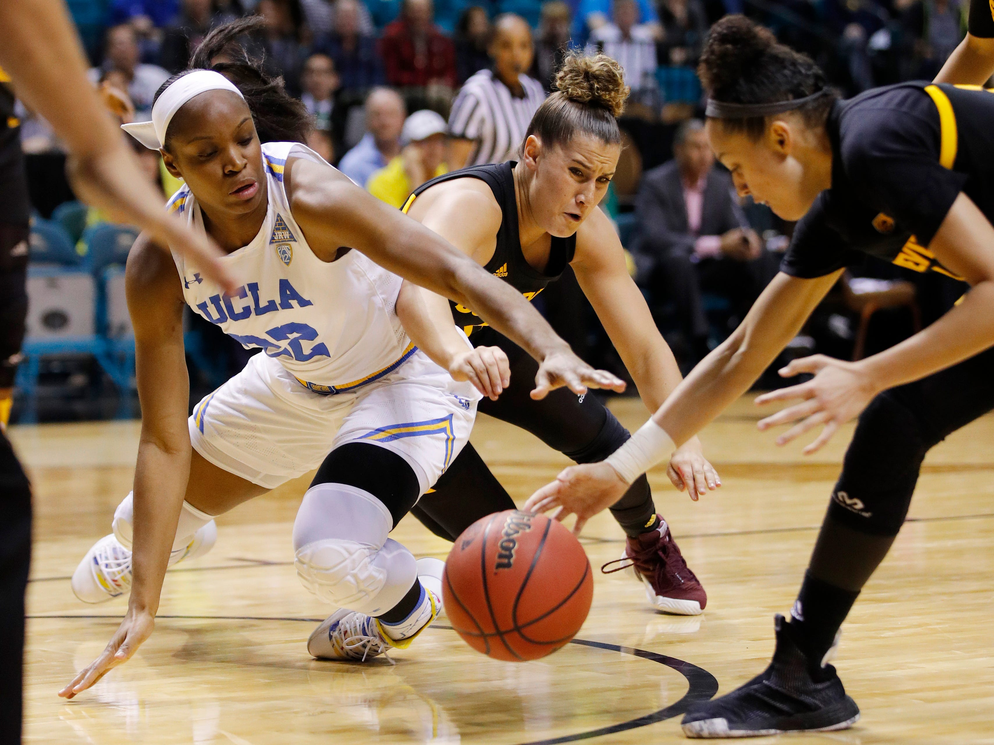From left, UCLA's Kennedy Burke, Arizona State's Taya Hanson and Reili Richardson scramble for the ball during the second half of an NCAA college basketball game at the Pac-12 women's tournament Friday, March 8, 2019, in Las Vegas.