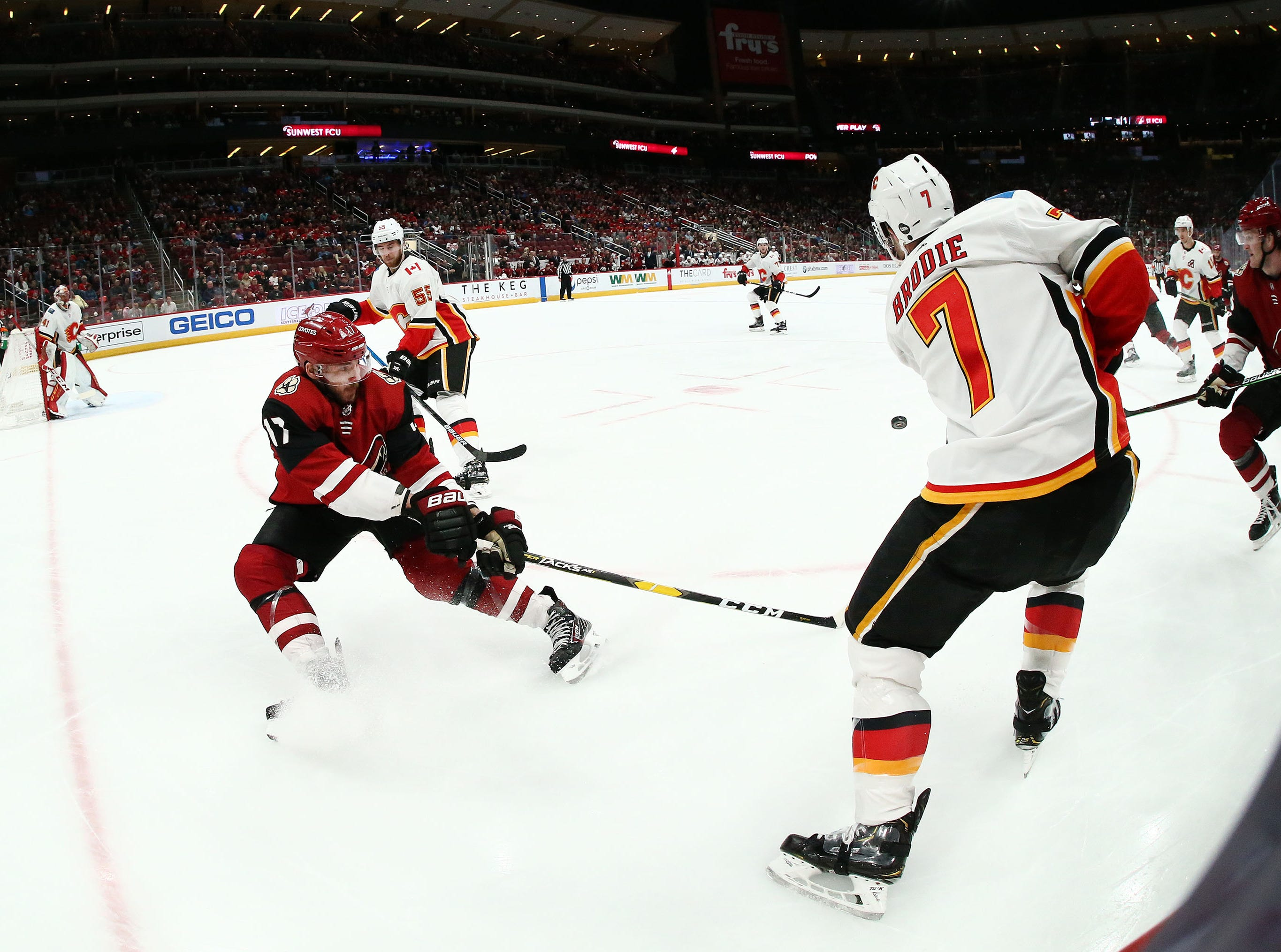 Calgary Flames defenseman TJ Brodie (7) passes the puck against Arizona Coyotes center Alex Galchenyuk (17) in the second period on Mar. 7, 2019, at Gila River Arena in Glendale, Ariz.