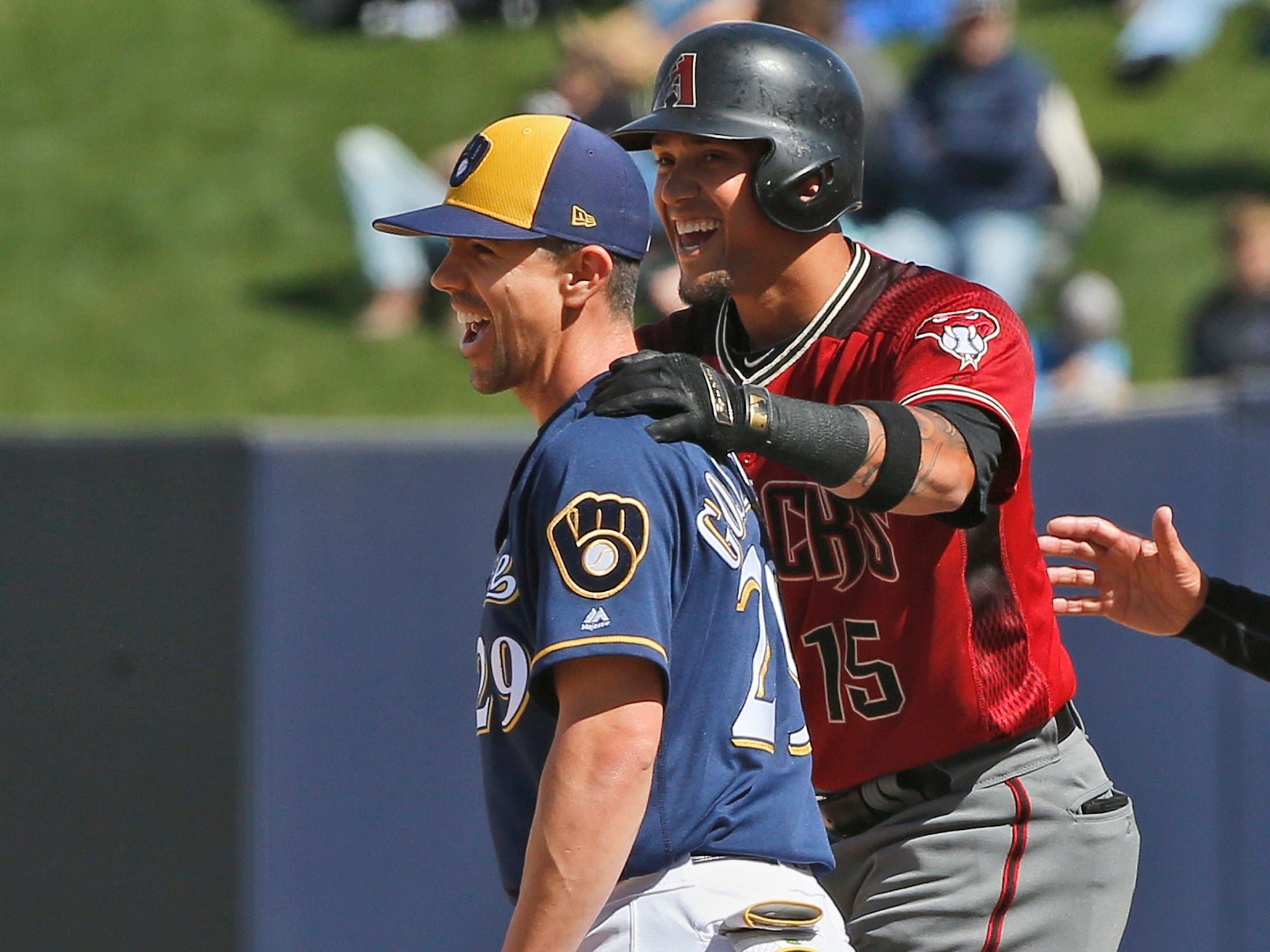 Arizona Diamondbacks' Ildemaro Vargas, right, laughs with Milwaukee Brewers' Tuffy Gosewisch, left, after reaching first base on a walk in the seventh inning of a spring training baseball game Friday, March 8, 2019, in Phoenix.