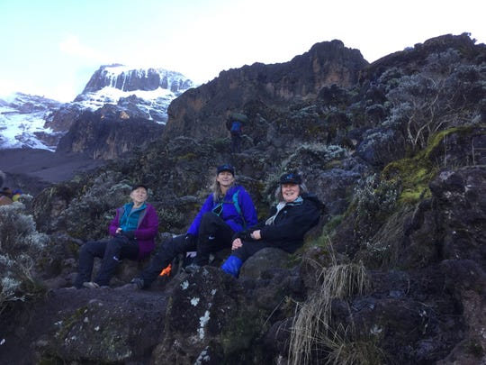 Betty Schley (left), Shaun Bennett (center) and Catherine Buick take a rest during their climb to the top of Mt. Kilimanjaro in February 2019.
