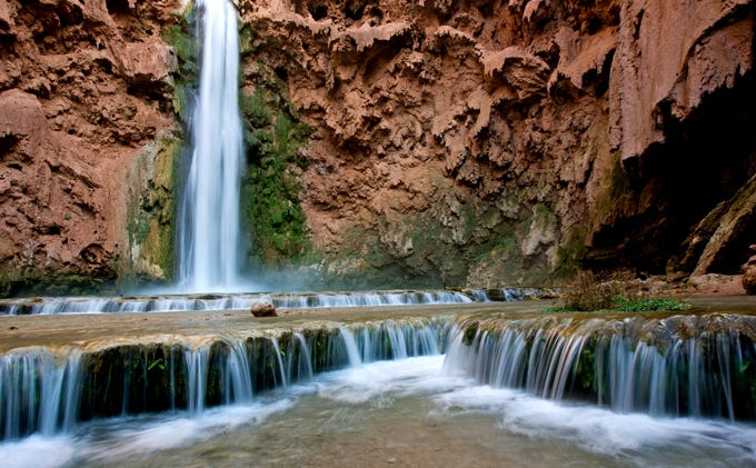 Water flows from Mooney Falls, one of the the Havasupai waterfalls. The waterfall is 220 feet tall, higher than Niagra Falls.
