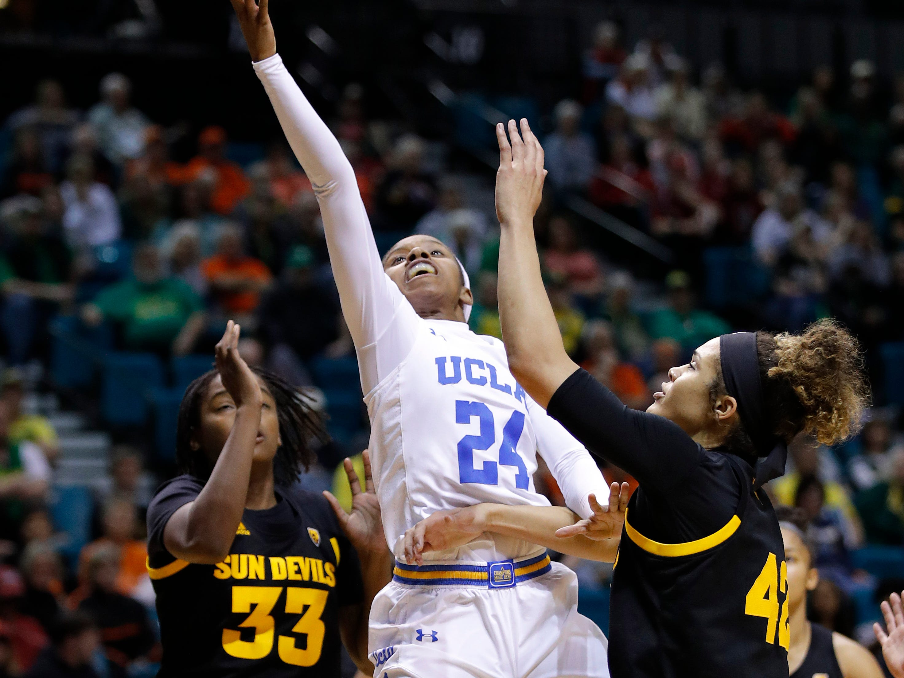UCLA's Japreece Dean shoots between Arizona State's Charnea Johnson-Chapman, left, and Kianna Ibis during the second half of an NCAA college basketball game at the Pac-12 women's tournament Friday, March 8, 2019, in Las Vegas.