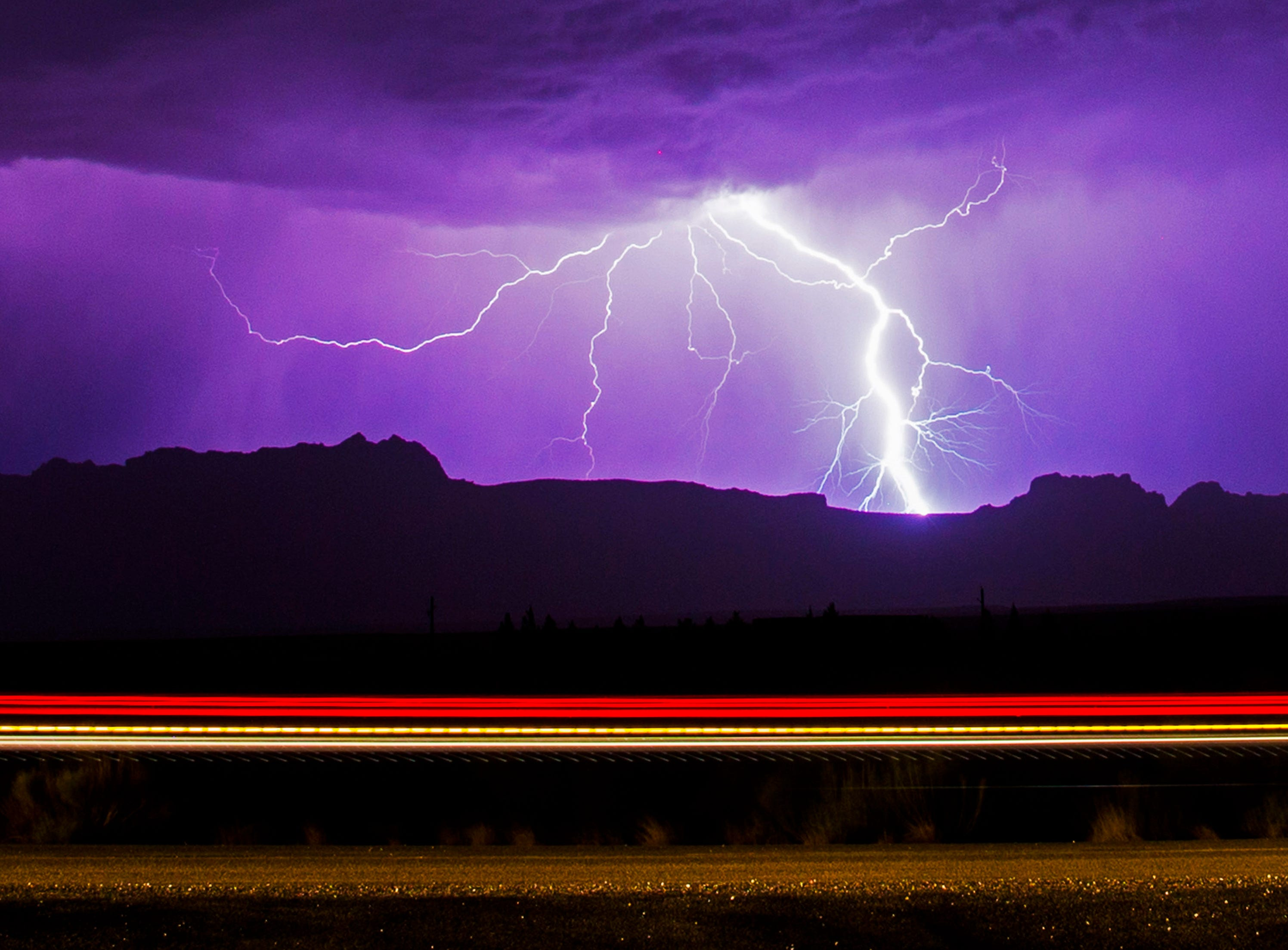 Lightning strikes over Echo Cliffs while lights from a car traveling on U.S. Route 89A illuminates the road in Northern, Ariz. July 10, 2018.