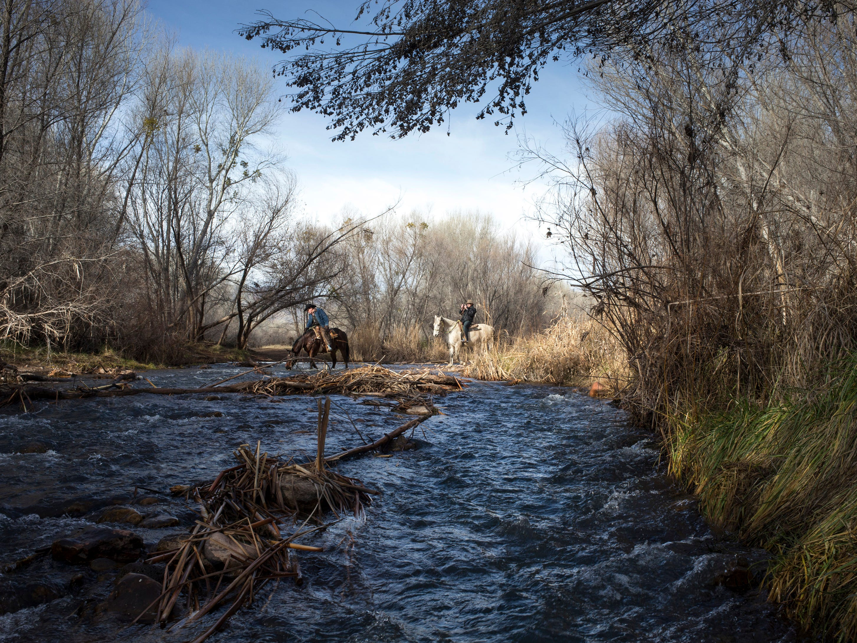 Jerry Couture (right) photographs Trail Horse Adventures guide Wild Bill Jones as they cross the Verde River, January 19, 2016, in Dead Horse Ranch State Park,675 Dead Horse Ranch Road, Cottonwood, Arizona.