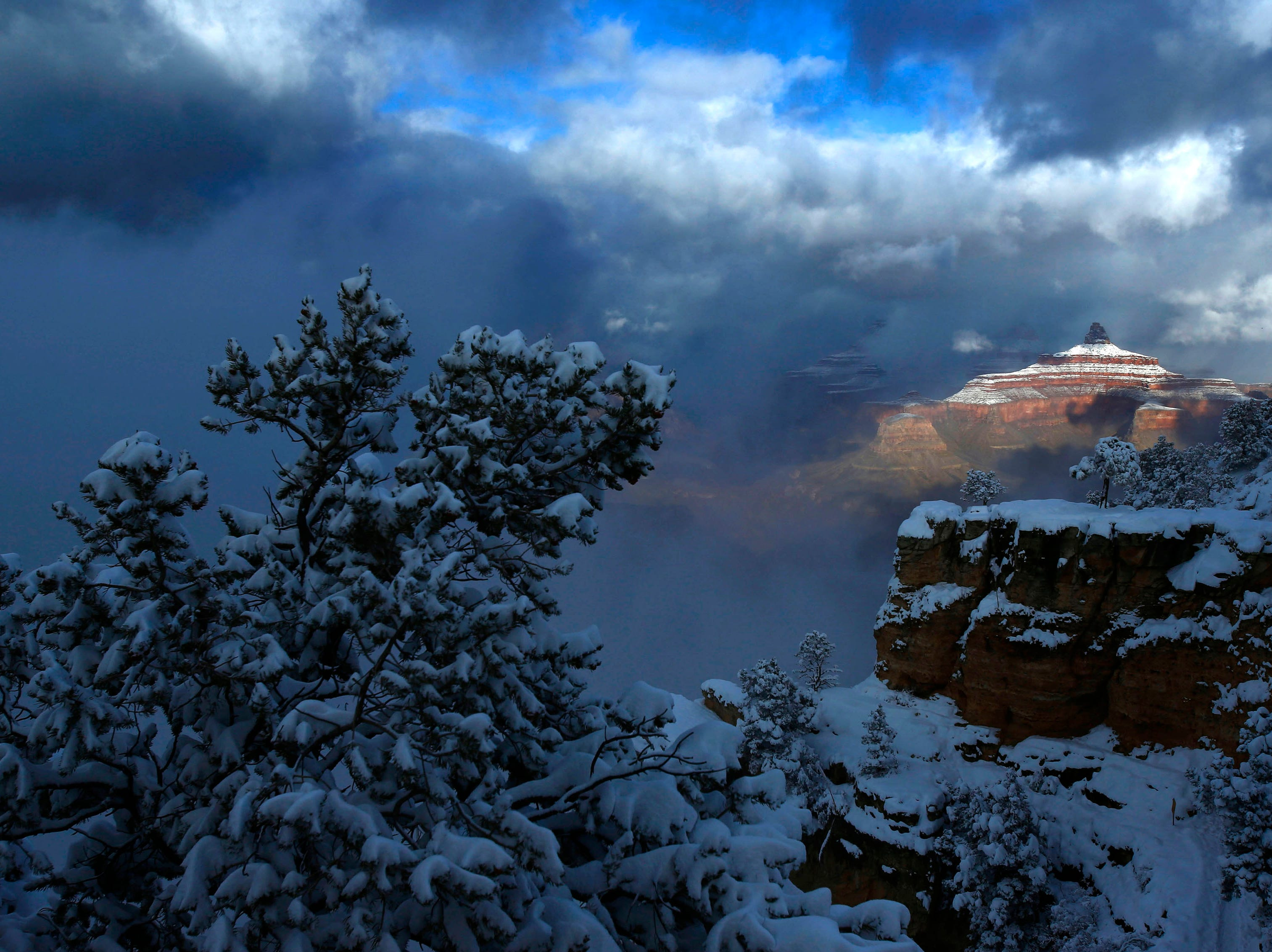 Sunshine breaks through the clouds and illuminates the rock formation Zoroaster Temple following a snow storm that passed over the Grand Canyon.