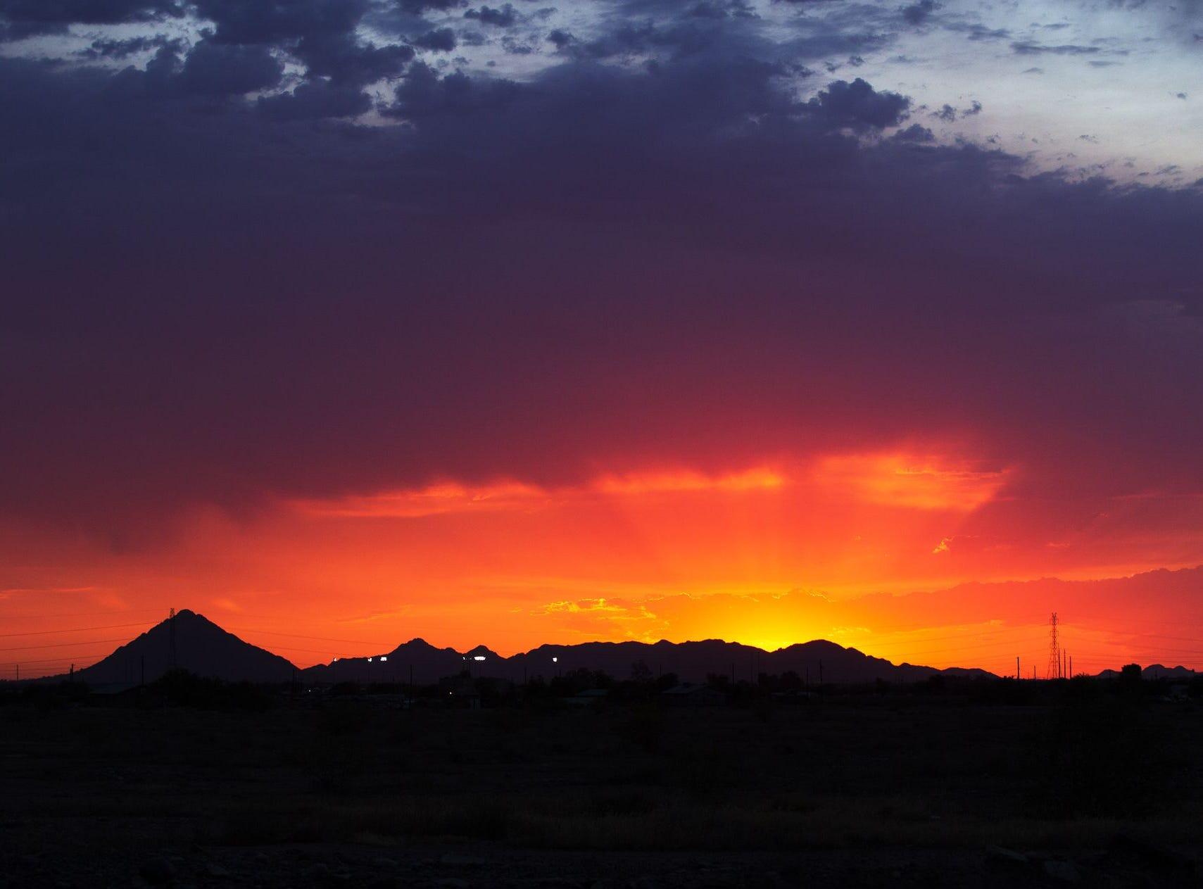 La puesta de sol brilla de color naranja brillante en el cielo sobre Phoenix, Arizona, el primer día del verano 20 de junio de 2016.