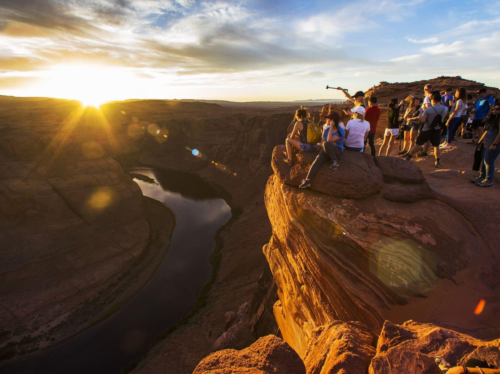 Los visitantes disfrutan de la puesta de sol desde Horseshoe Bend cerca de Page, Arizona, 9 de mayo de 2018.