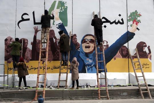 Mujeres en Afganistán elaboran un mural alusivo a la libertad de la mujer.