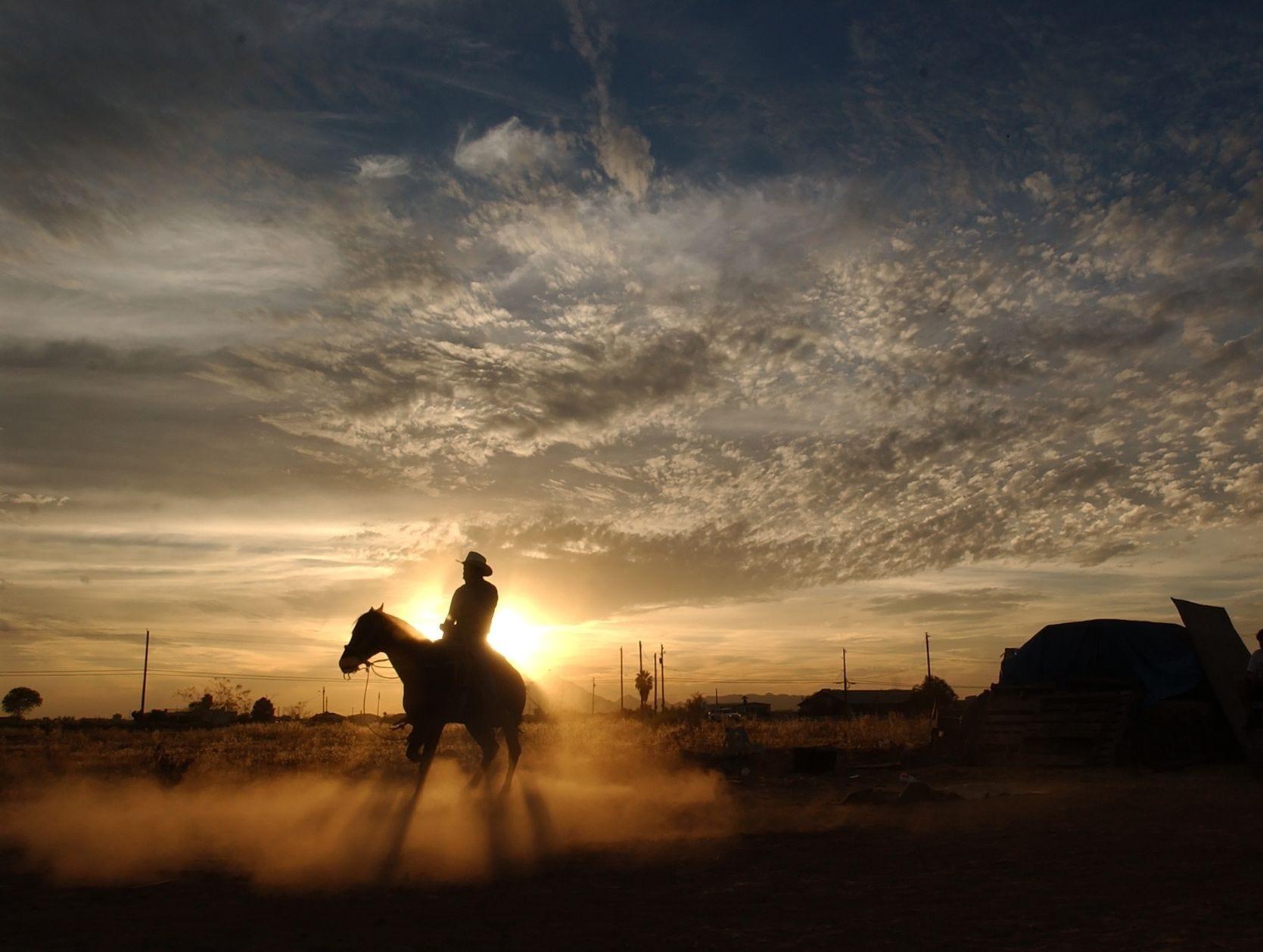 Con la puesta de sol detrás de él, Pascual Valadez, de 35 años, monta su caballo en trueno mientras lo entrena en la casa de su hermano en la comunidad indígena de Salt River Pima-Maricopa el lunes 12 de mayo.
