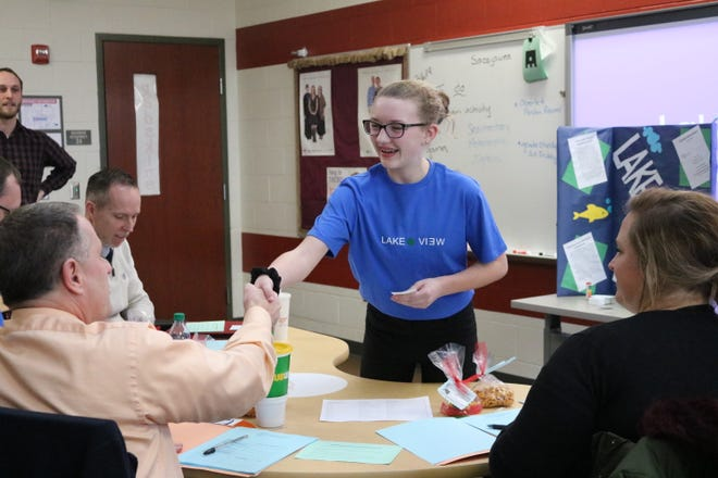 "Maddie Wiechman, a seventh grader at PCMS, offers a handshake to Mike Zipfel, a business teacher at PCHS and guest judge in the Young Entrepreneurs' ""Shark Tank"" event on Wednesday."