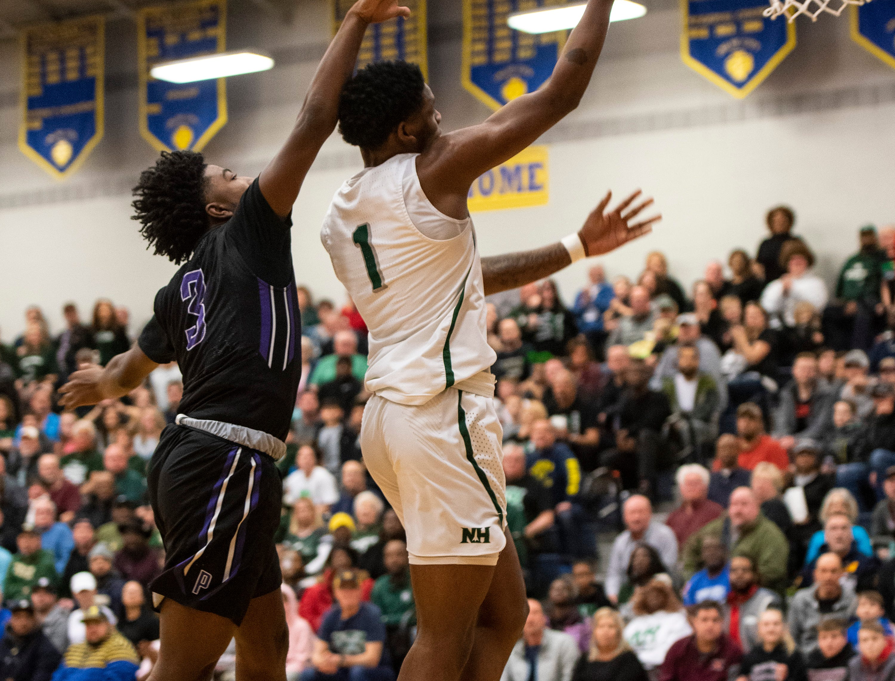 Pontiac High School's Ernesto Simpson Jr (3) reaches over New Haven's Romeo Weems to attempt to block a shot in the MHSAA Division 2 regional basketball finals Thursday, March 7, 2019 at Imlay City High School.