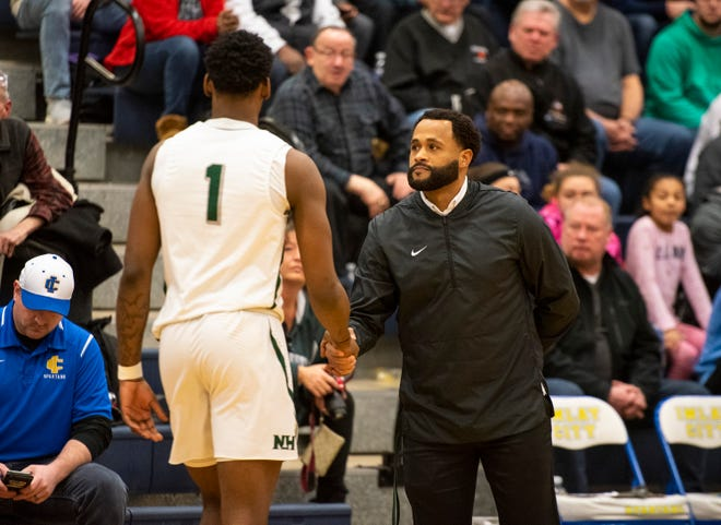New Haven High School head coach Tedaro France, right, shakes hands with Romeo Weems before the MHSAA Division 2 regional basketball finals against Pontiac High School Thursday, March 7, 2019 at Imlay City High School.