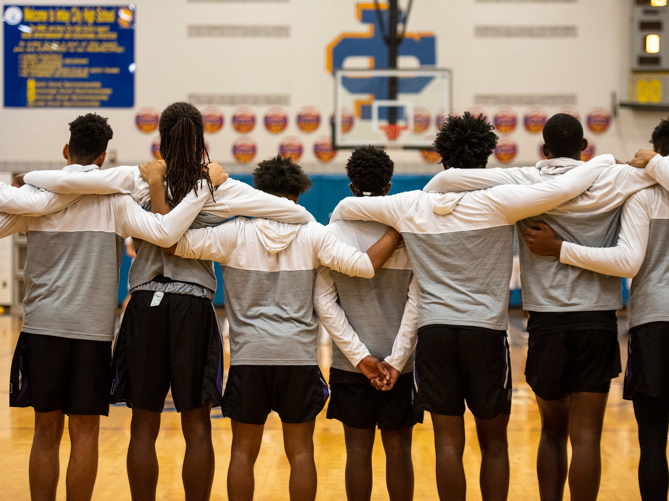 Members of the New Haven High School basketball team link up before the National Anthem at the start of the MHSAA Division 2 regional basketball finals against Pontiac High School Thursday, March 7, 2019 at Imlay City High School.