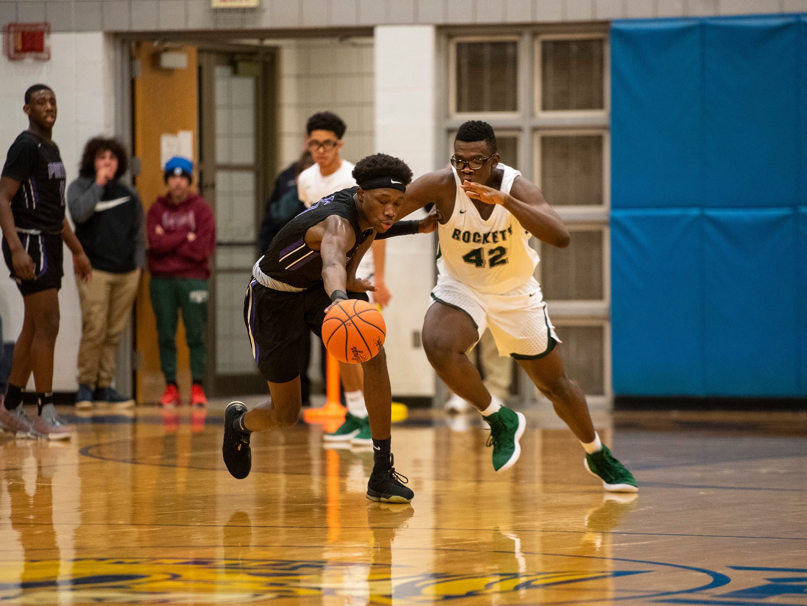 New Haven's Malen Lewis (42) and Pontiac's Dominique Stovall chase a loose ball in the MHSAA Division 2 regional basketball finals Thursday, March 7, 2019 at Imlay City High School.