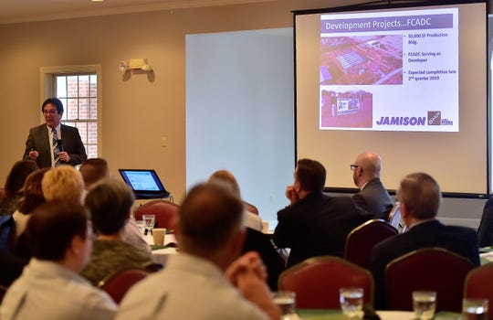 Franklin County Area Development Corporation President Mike Ross talks to a large audience of local business, nonprofit, municipal and political figures at the organization's State of the Economy breakfast on Thursday at Chambersburg Country Club. On the screen to his right is a presentation slide on Jamison Door Company, a Hagerstown, Md. -based company that is in the process of opening another location in Wharf Road Industrial Park near Waynesboro.
