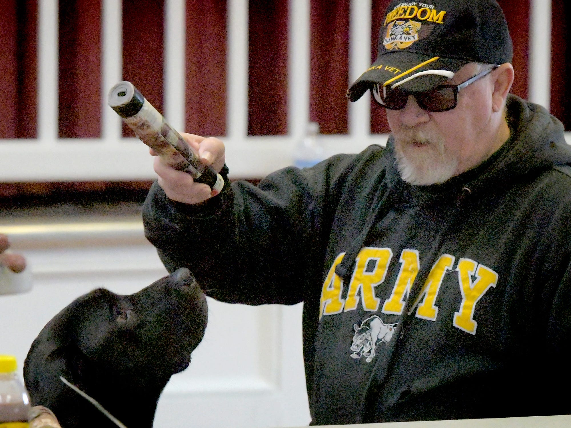 "Class assistant George Mong plays with Bob Fink's pit bull/golden retriever ""Johnny Cash"" during a training session at Trinity Lutheran Church in East Berlin Thursday, March 7, 2019. Mong was helping lead a session with Fink offered by Cover Six Canines, a ministry of Freedom Biker Church York, which gives free service dog training to veterans. Bill Kalina photo"