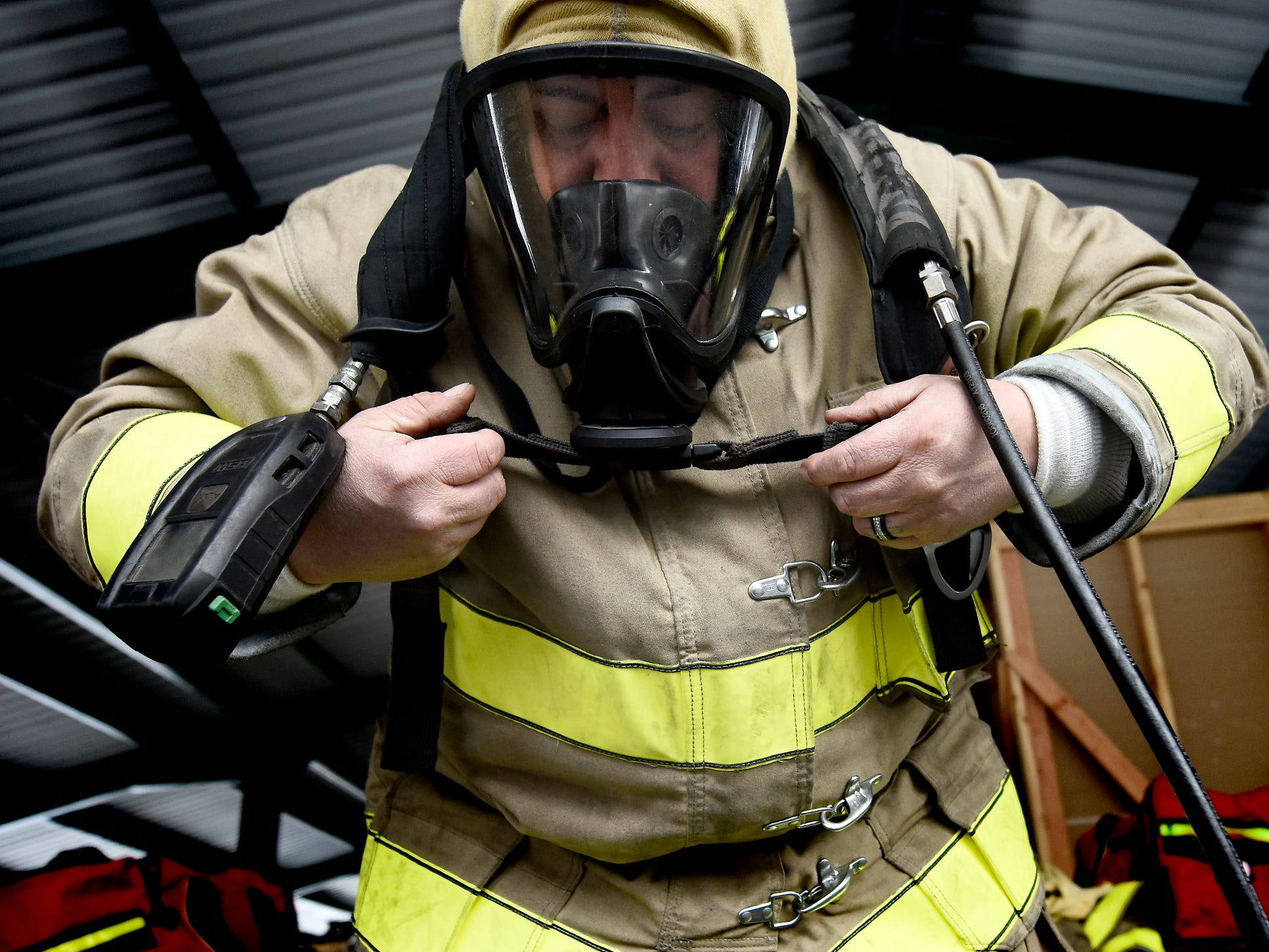 York County Prison corrections officer Juan Canales dons gear while preparing for a fire scenario at the York County Fire School during training there Friday, March 8, 2019. Members of the prison's 30-member Fire Emergency Response Team were completing a 40-hour fire training course at the school. The team is designed to control fire emergencies onsite prior to the arrival of firefighters. Bill Kalina photo