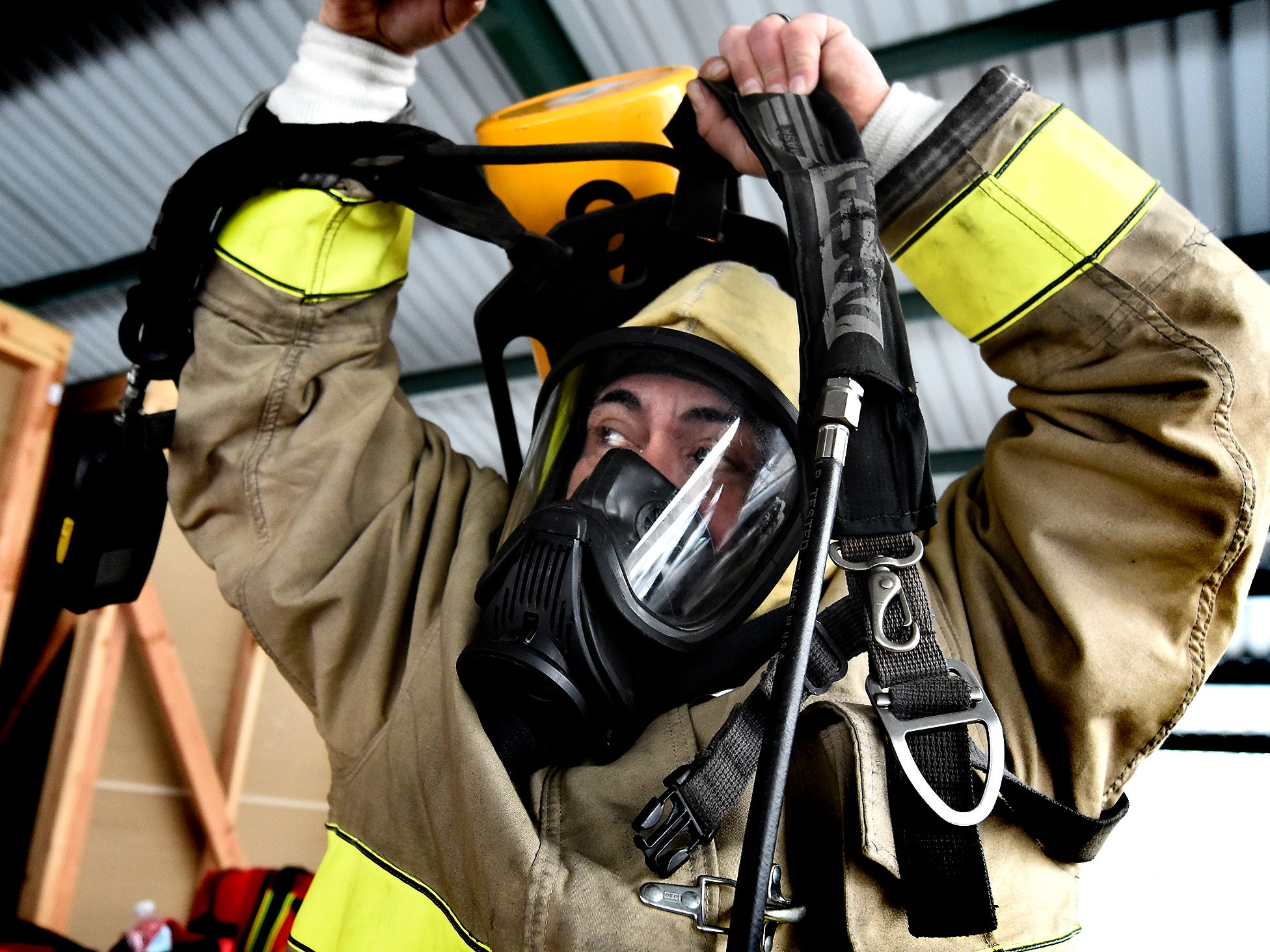 York County Prison corrections officer Juan Canales dons gear while preparing for a fire scenario at the York County Fire School during training there Friday, March 8, 2019. Members of the prison's 30-member Fire Emergency Response Team were completing a 40-hour fire training course at the school. The FERT team is designed to control fire emergencies onsite prior to the arrival of firefighters. Bill Kalina photo