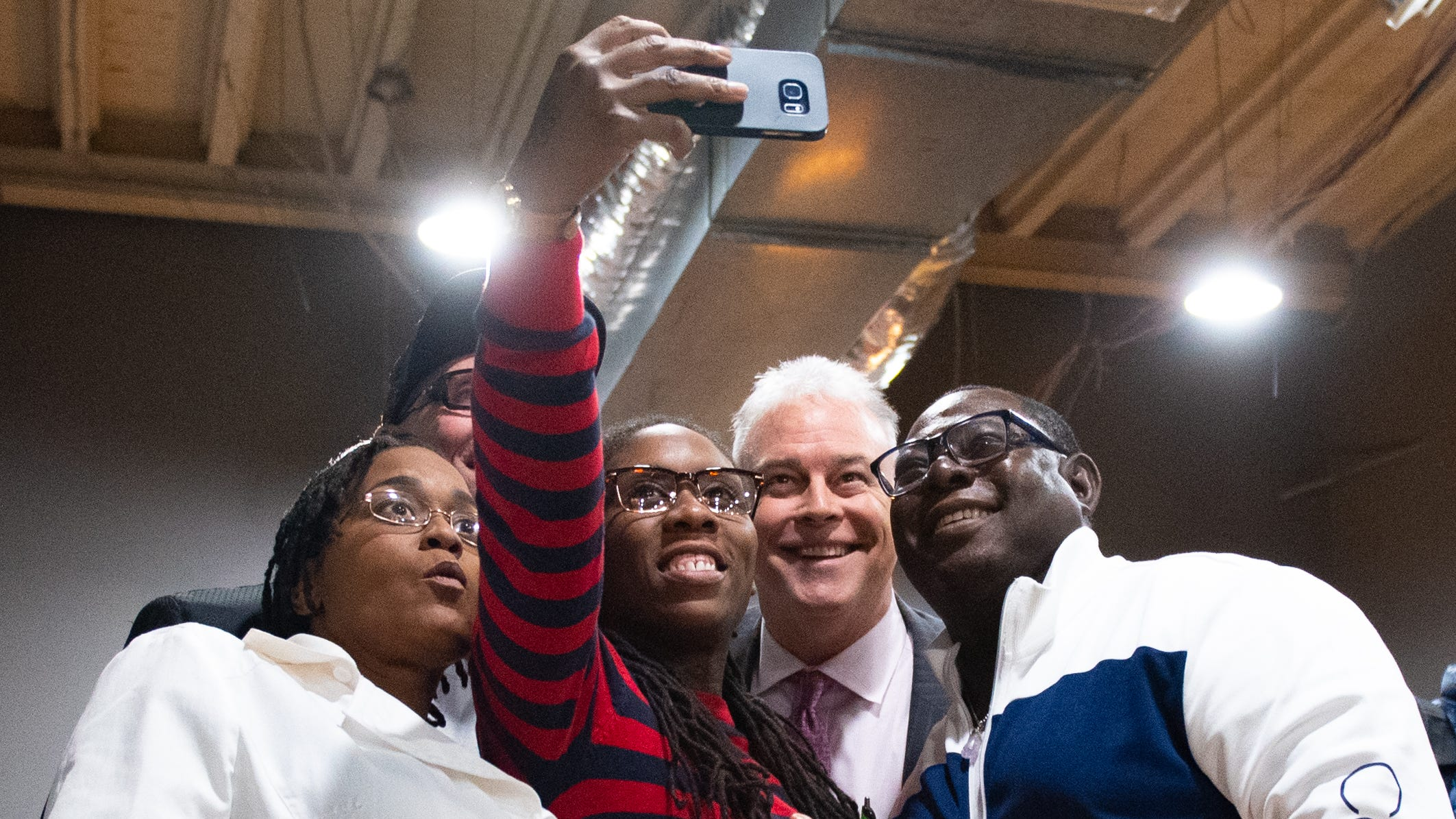 April Collier takes a selfie with party goers during the Jook Joint Global Inc. and LEXI Social Club grand opening, March 7, 2019.