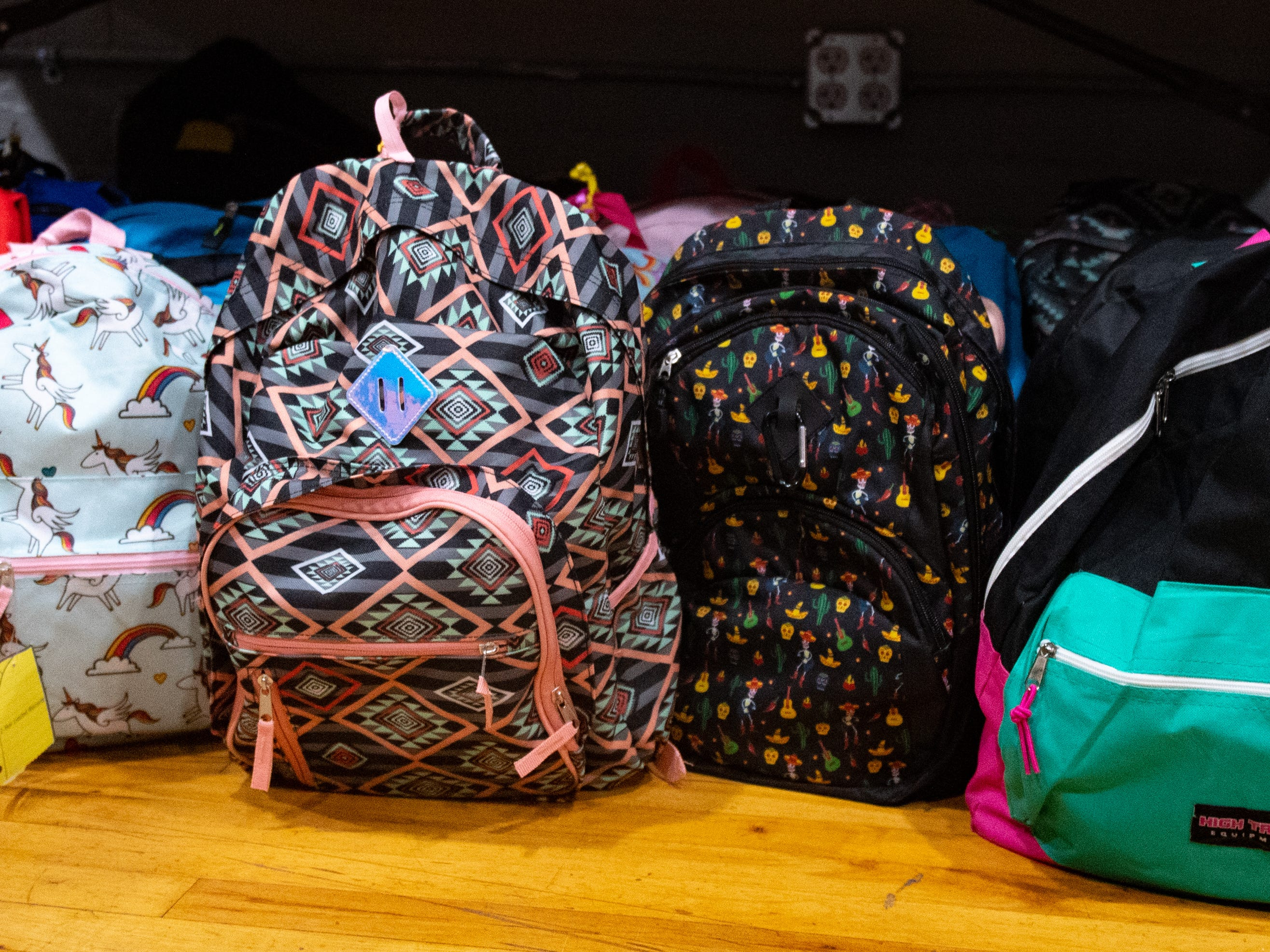 Backpacks sit in the corner as children play during the Jook Joint Global Inc. and LEXI Social Club grand opening, March 7, 2019.