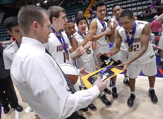 Aquinas head coach Michael Grosodonia, left, hands the championship plaque to Jalen Pickett following the Class AA final of the 2016 NYSPHSAA Boys Basketball Championships held at the Glens Falls Civic Center in Glens Falls, N.Y. on Sunday, March 13, 2016. Aquinas took the Class AA title with a 68-50 win over Middletown-IX. Grosodonia is now the coach at St. John Fisher and Pickett is a star for Siena.