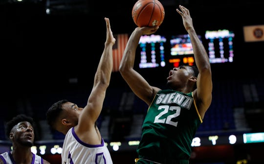Aquinas graduate Siena  guard Jalen Pickett (22) shoots against Patrick Benzan and Chris Lovisolo of Holy Cross earlier this season. Pickett was the first freshman in 32 years to be named first-team All-MAAC.