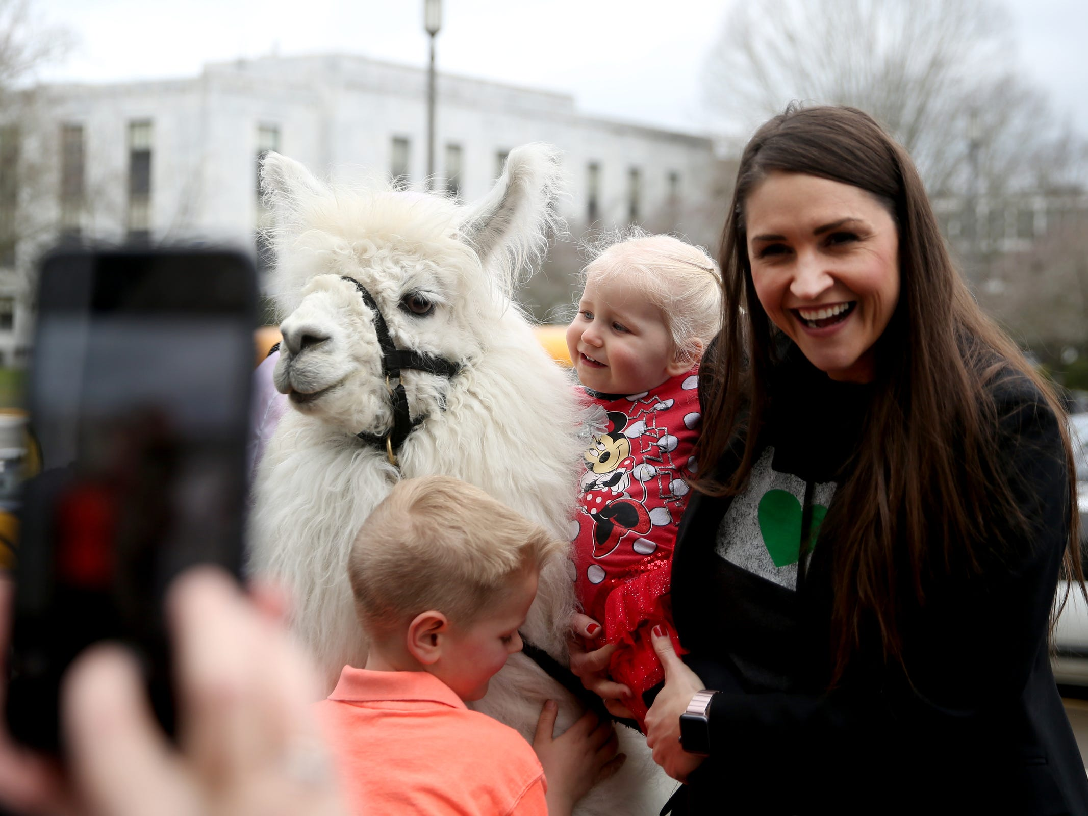 Sen. Shemia Fagan, D-Portland, has a photo taken with her children, Alton, 6, and Imogene Maughan, 2, with Caesar the No Drama Llama during a demonstration for International Women's Day at the Oregon State Capitol in Salem on Friday, March 8, 2019. Many during the rally voiced their support for a state-run family and medical leave insurance program in Oregon.