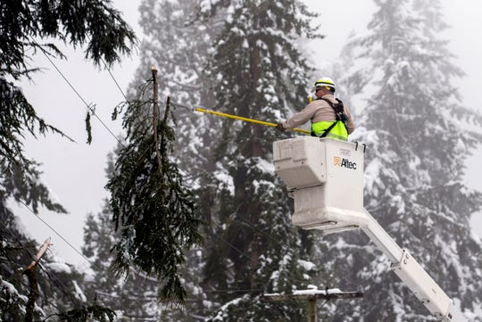 Eugene Water and Electric Board electric trouble shooter Brian Shepherd cuts a limb while trying to free it from a line along Friendly Street in Eugene, Ore., February 26, 2019. The utility continues work to restore power outages caused by the heavy snowfall.