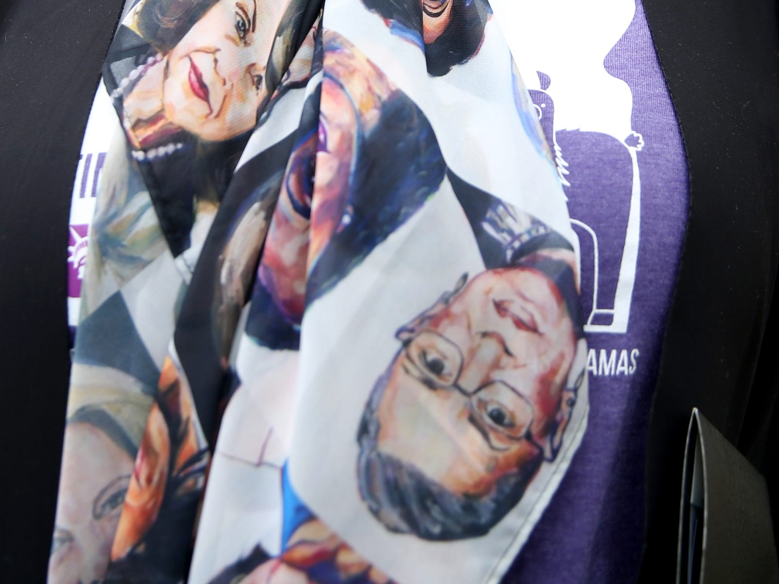Dacia Grayber, of Tigard, wears a scarf with the faces of prominent women during a demonstration for International Women's Day at the Oregon State Capitol in Salem on Friday, March 8, 2019. Many during the rally voiced their support for a state-run family and medical leave insurance program in Oregon.