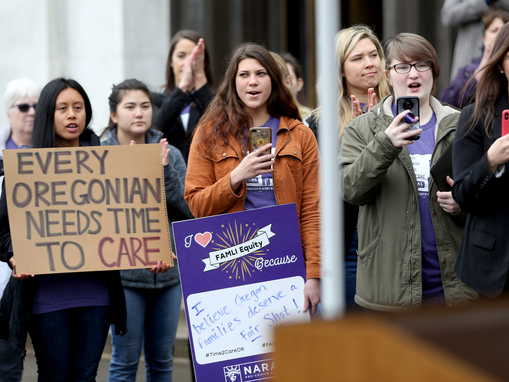 Malaya Lualhati, from left, of Corvallis, Kyana Wigen, of Corvallis, Marial Vellinga, of Salem, and others attend a demonstration for International Women's Day at the Oregon State Capitol in Salem on Friday, March 8, 2019. Many during the rally voiced their support for a state-run family and medical leave insurance program in Oregon.
