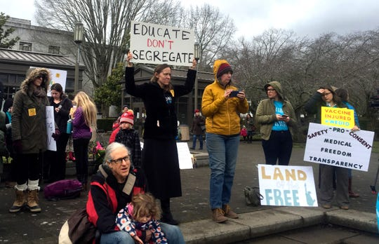 Hundreds of people, including families, attend a rally at the Oregon State Capitol protesting a proposal to tighten school vaccine requirements Thursday, March 7, 2019, in Salem, Ore. The measure would only allow students to opt out of vaccines if they have a doctor's note seeking an exemption for medical reasons.